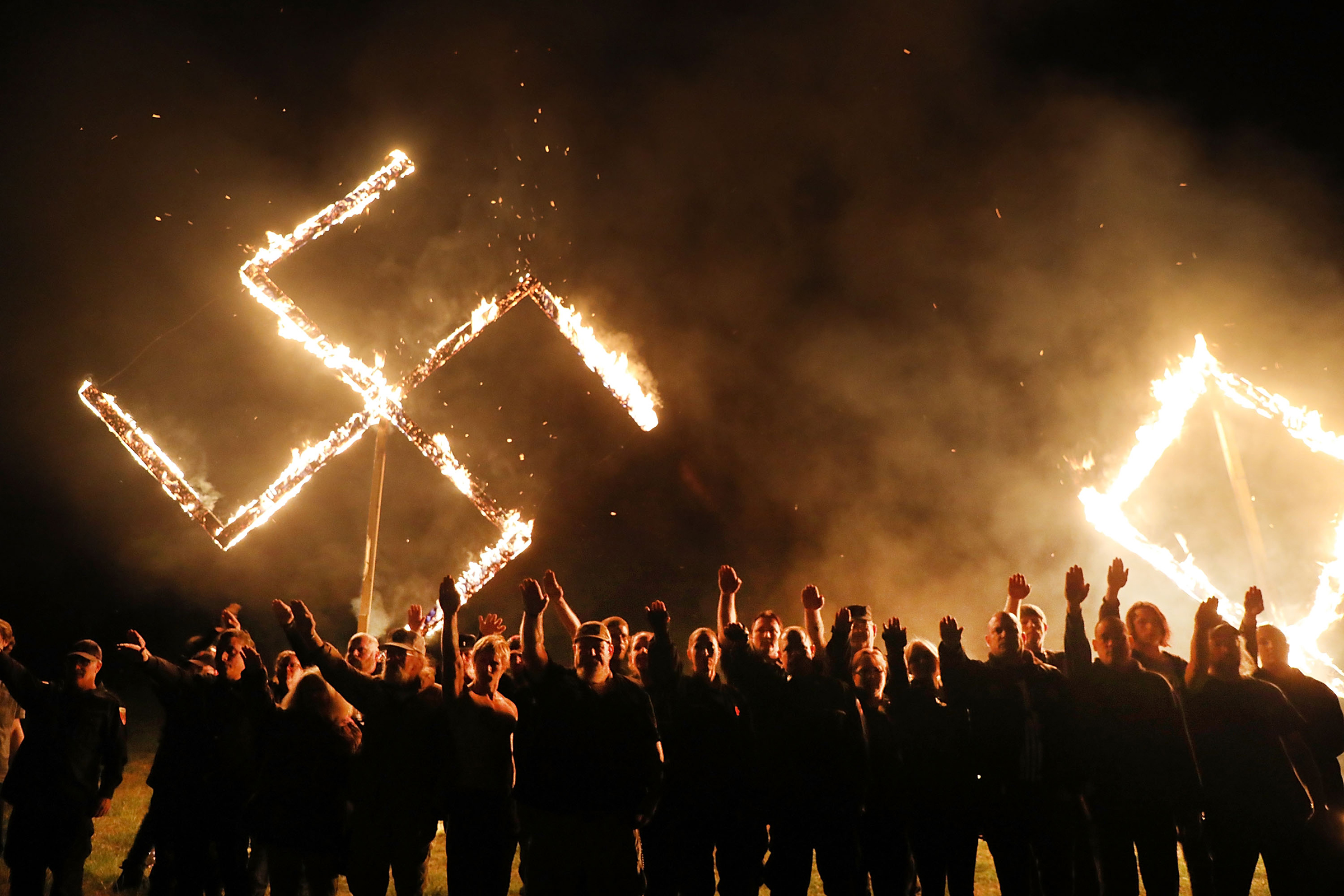 Members  of the National Socialist Movement, one of the largest neo-Nazi groups in the US, hold a swastika burning on April 21, 2018 in Draketown, Georgia.