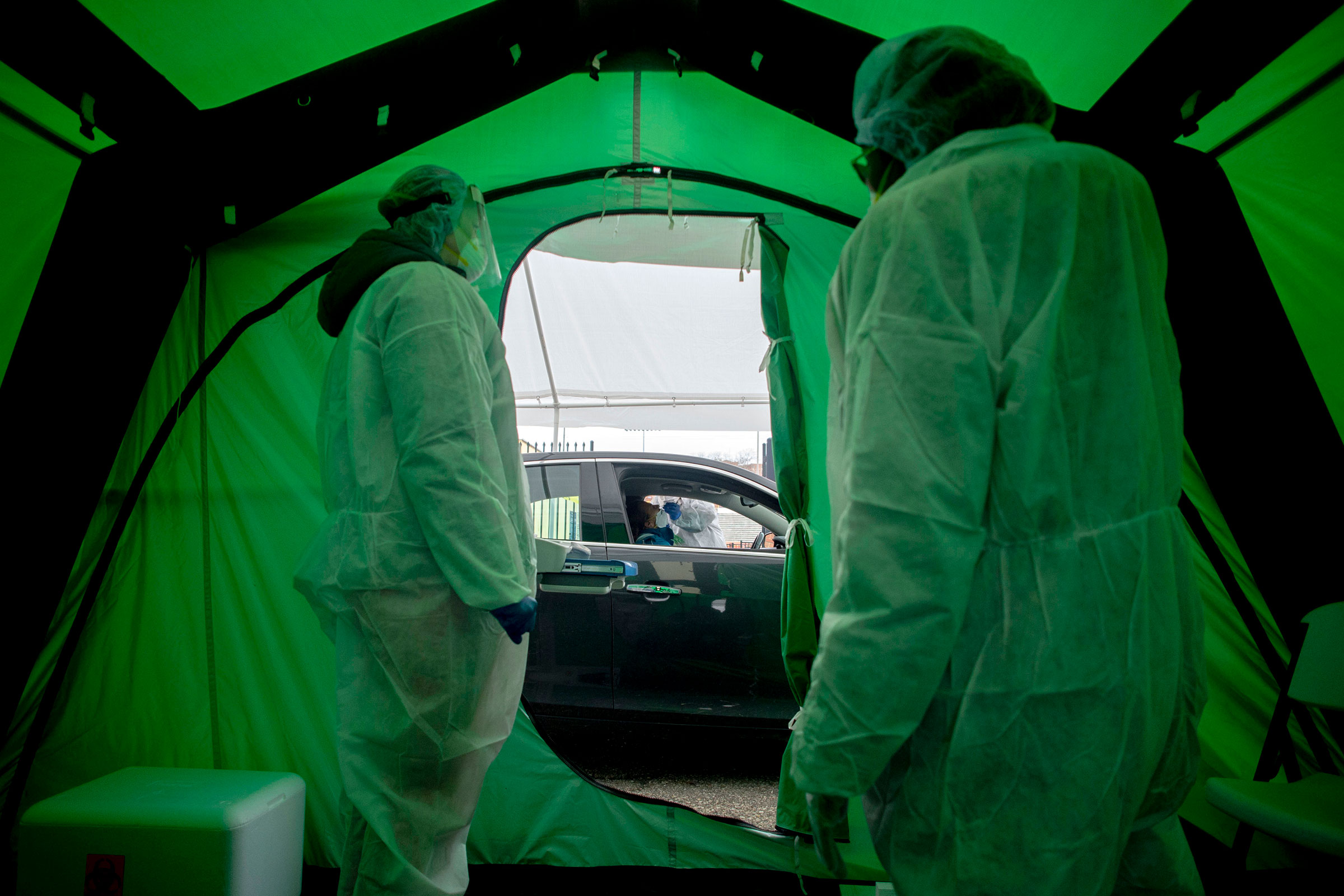 Medical workers watch as one of the first 50 people are tested for coronavirus at Flint, Michigan's first drive-thru testing site on April 15, 2020.