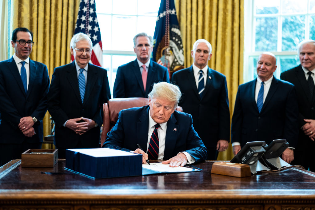 U.S. President Donald Trump signs H.R. 748, the CARES Act in the Oval Office of the White House on March 27, 2020 in Washington, DC.
