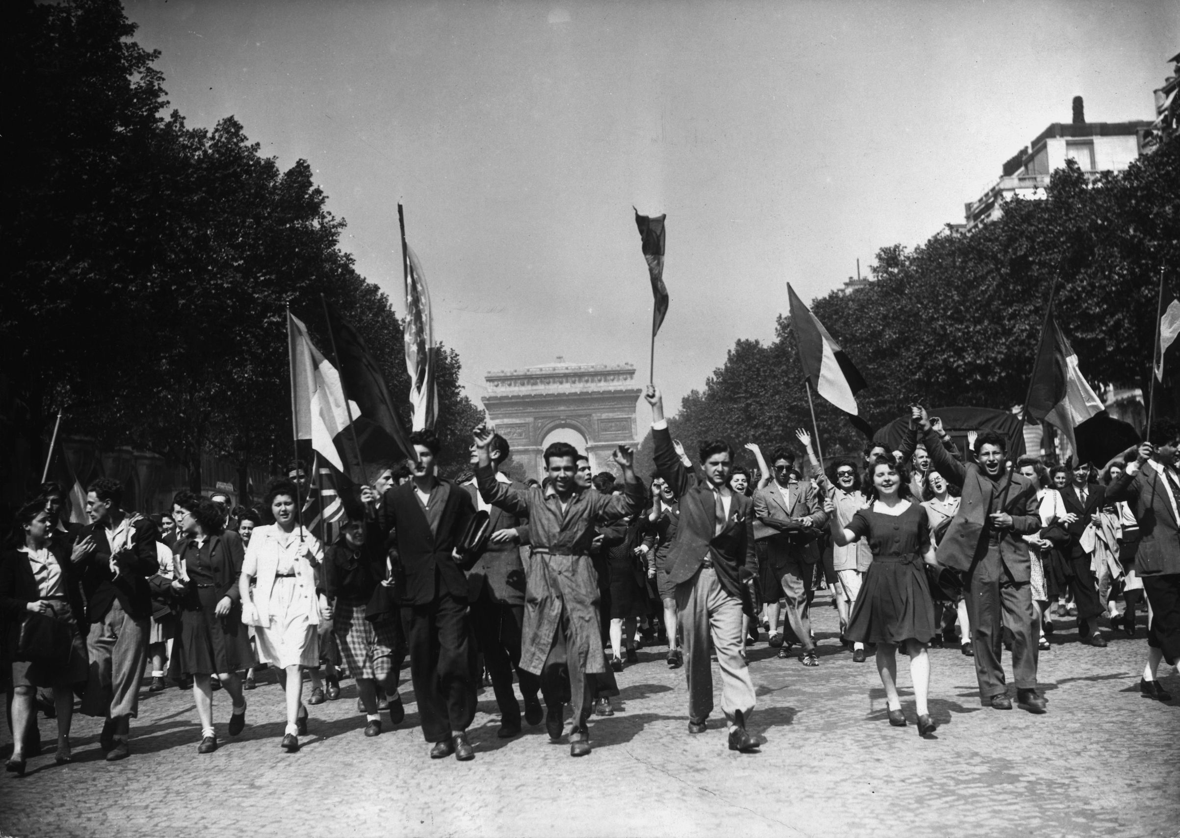 Crowds on the Champs-Élysées celebrate Victory in Europe at the end of World War II with a joyful procession on May 8, 1945