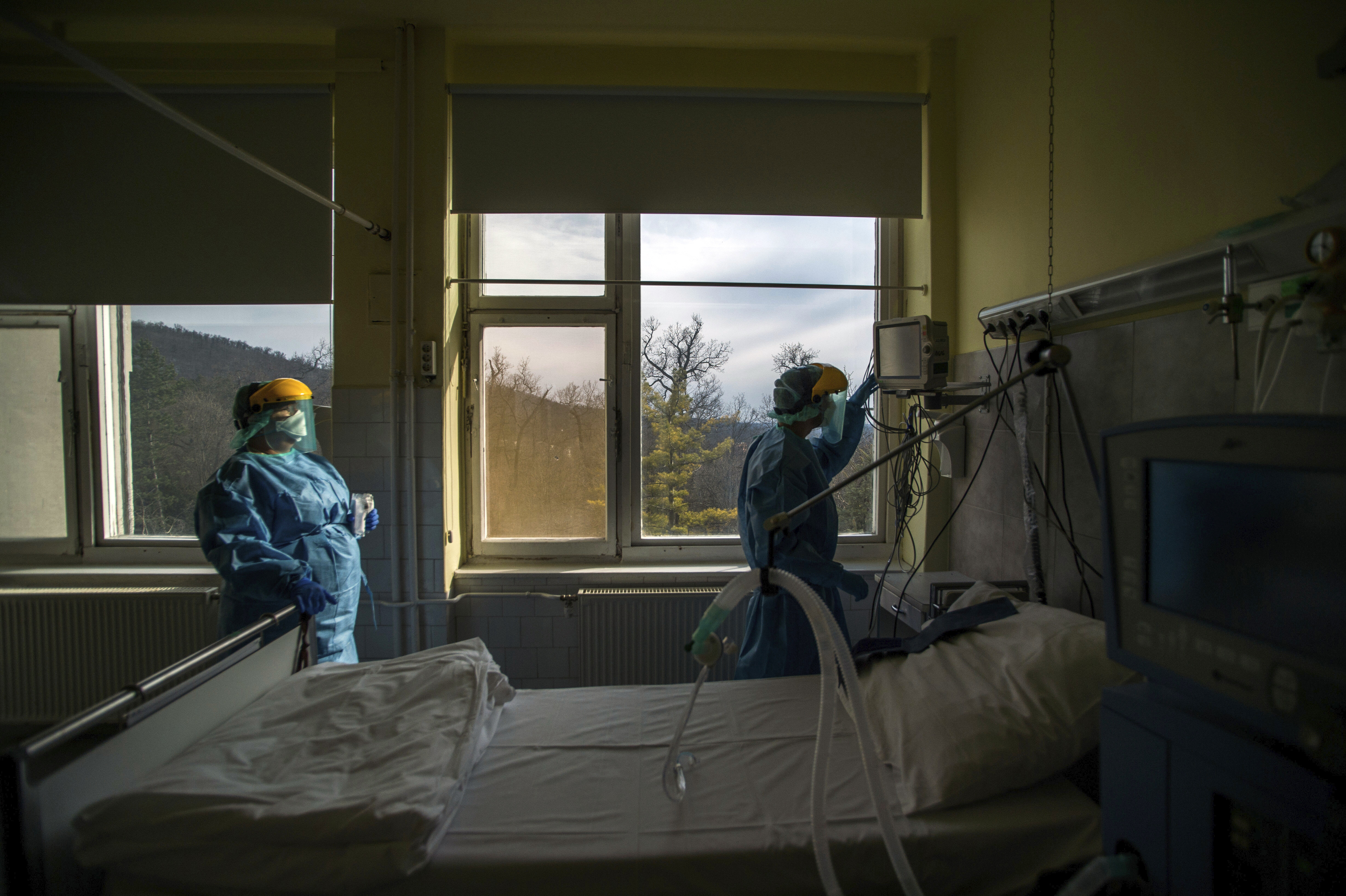 Medical staff members check a ventilator in protective suits at the care unit for the new COVID-19 infected patients inside the Koranyi National Institute of Pulmonology in Budapest on March 24, 2020.