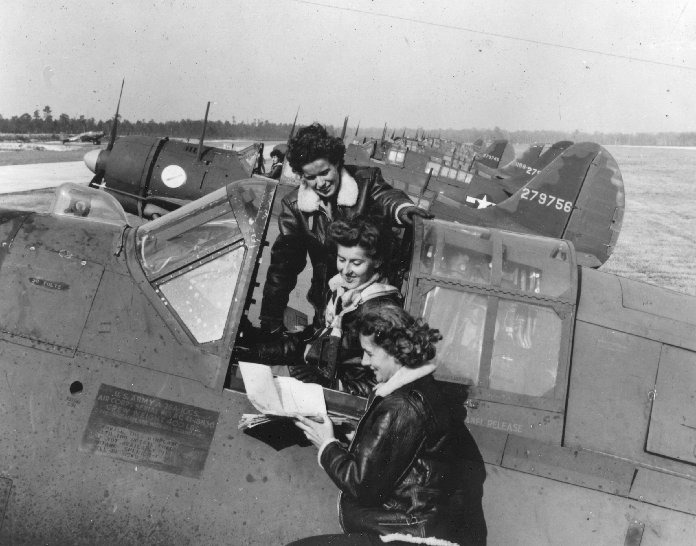 A trio of WASP around a Curtiss A-25A making last minute check-ups before taking off. Army Air Field Camp Davis, N.C. Circa 1944.