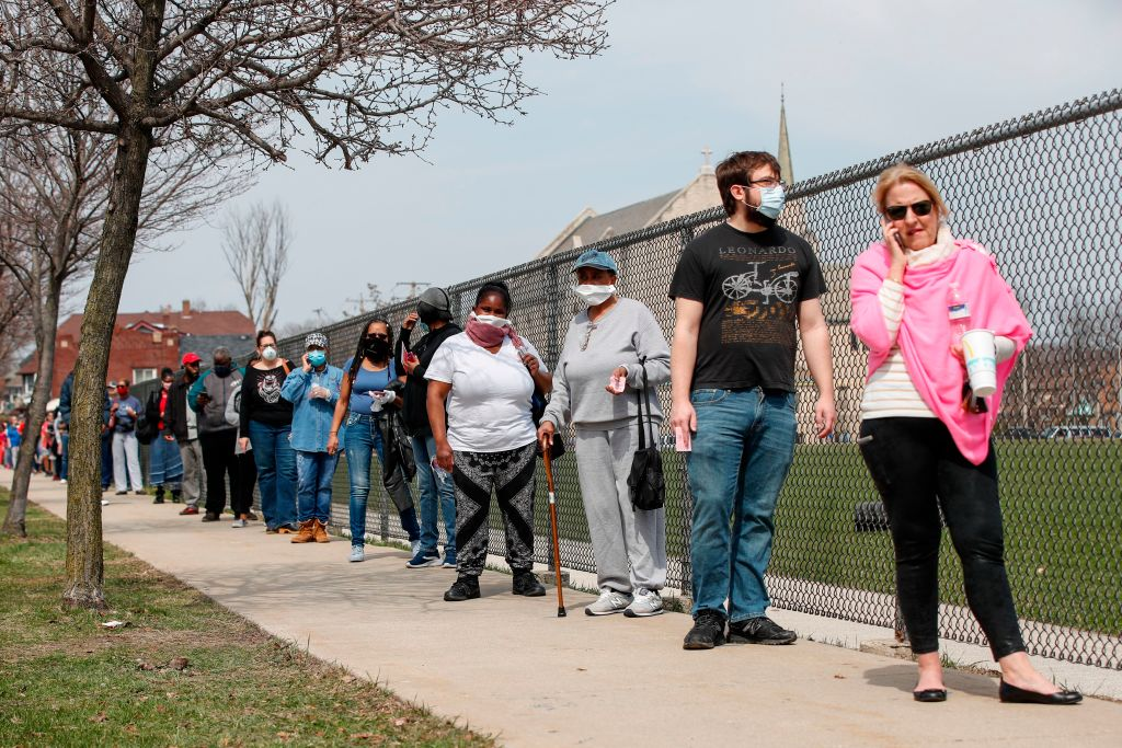 Residents wait in line to vote in a presidential primary election outside the Riverside High School in Milwaukee, Wisconsin on April 7, 2020.