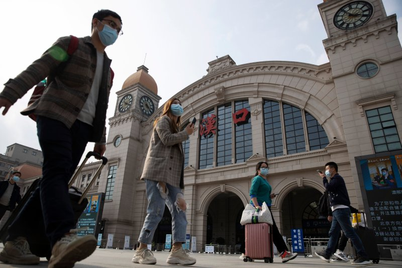 Travelers with their luggage walk past the Hankou railway station on the eve of its resuming outbound traffic in Wuhan in central China's Hubei province on April 7, 2020.