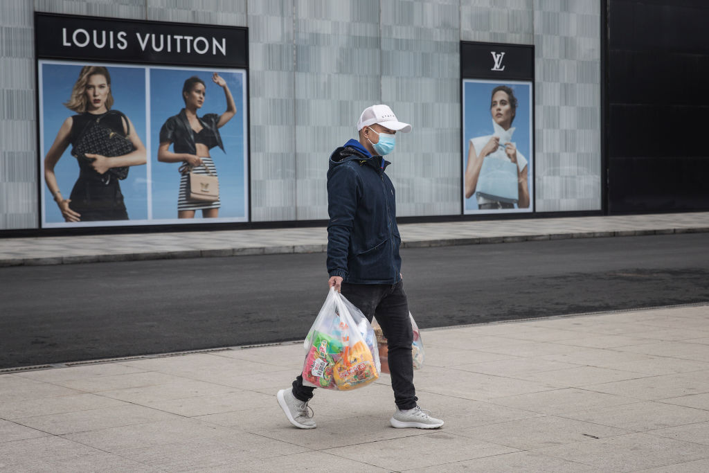 A man wearing a face mask passes a Louis Vuitton store outside Wuhan international plaza on March 30, 2020 in Hubei Province, China.