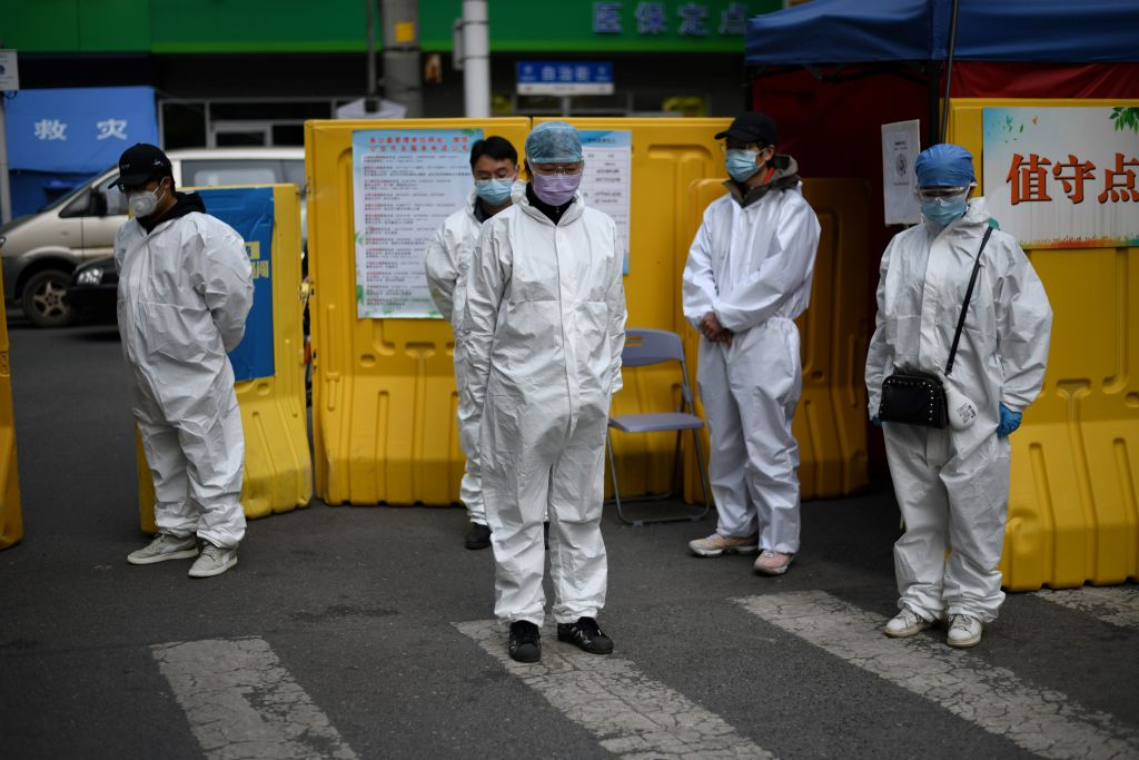Community volunteers wearing hazmat suits observe three minutes of silence to mourn those who died in the fight against the pandemic along a street in Wuhan, in Chinas central Hubei province on April 4, 2020. - China came to a standstill to mourn patients and medical staff killed by the coronavirus, with the world's most populous country observing a nationwide three-minute silence.