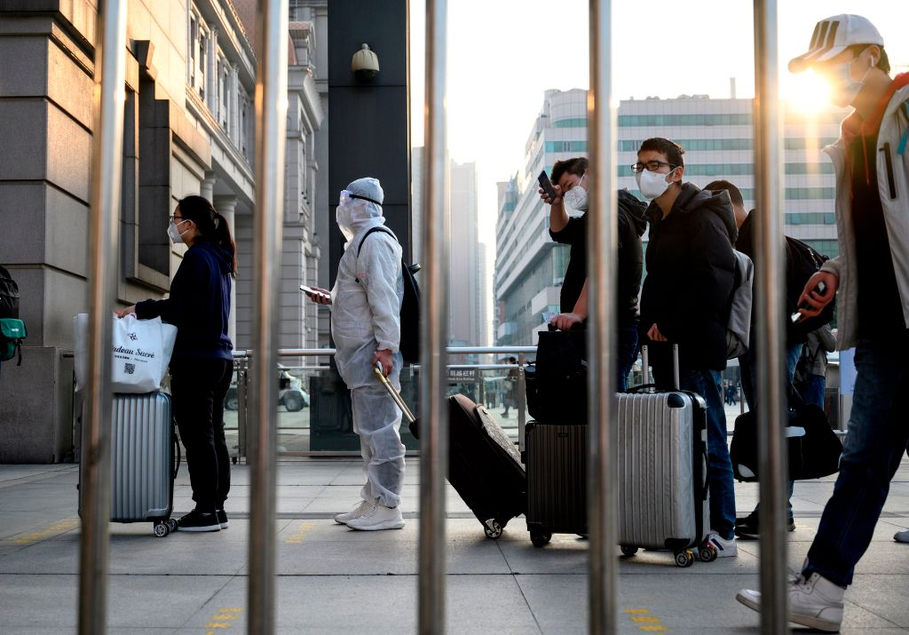 People wearing face masks arrive at Hankou Railway Station in Wuhan to take one of the first trains leaving the city in China's central Hubei province early on April 8, 2020.