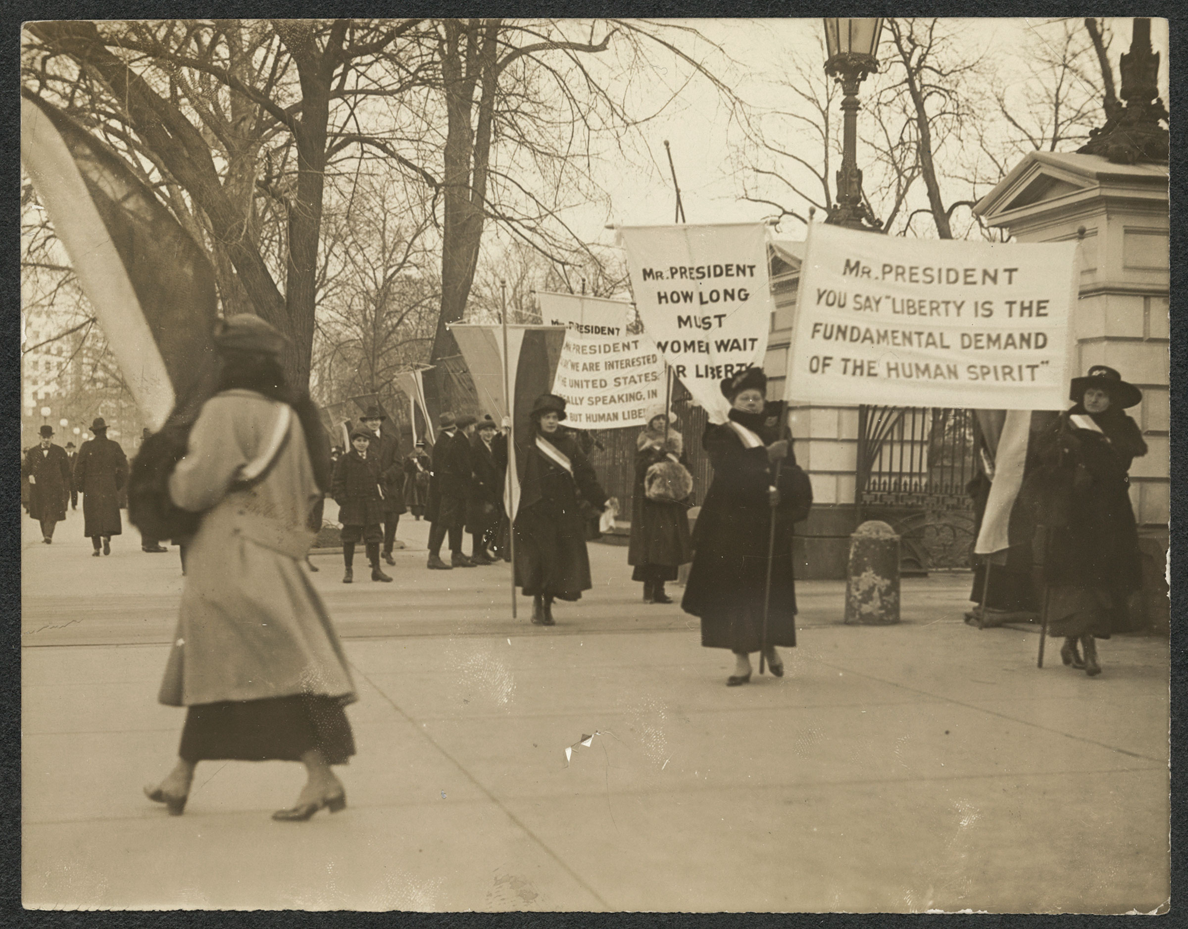 Suffragists picket with banners on the sidewalk in front of White House gates on Jan. 26, 1917.