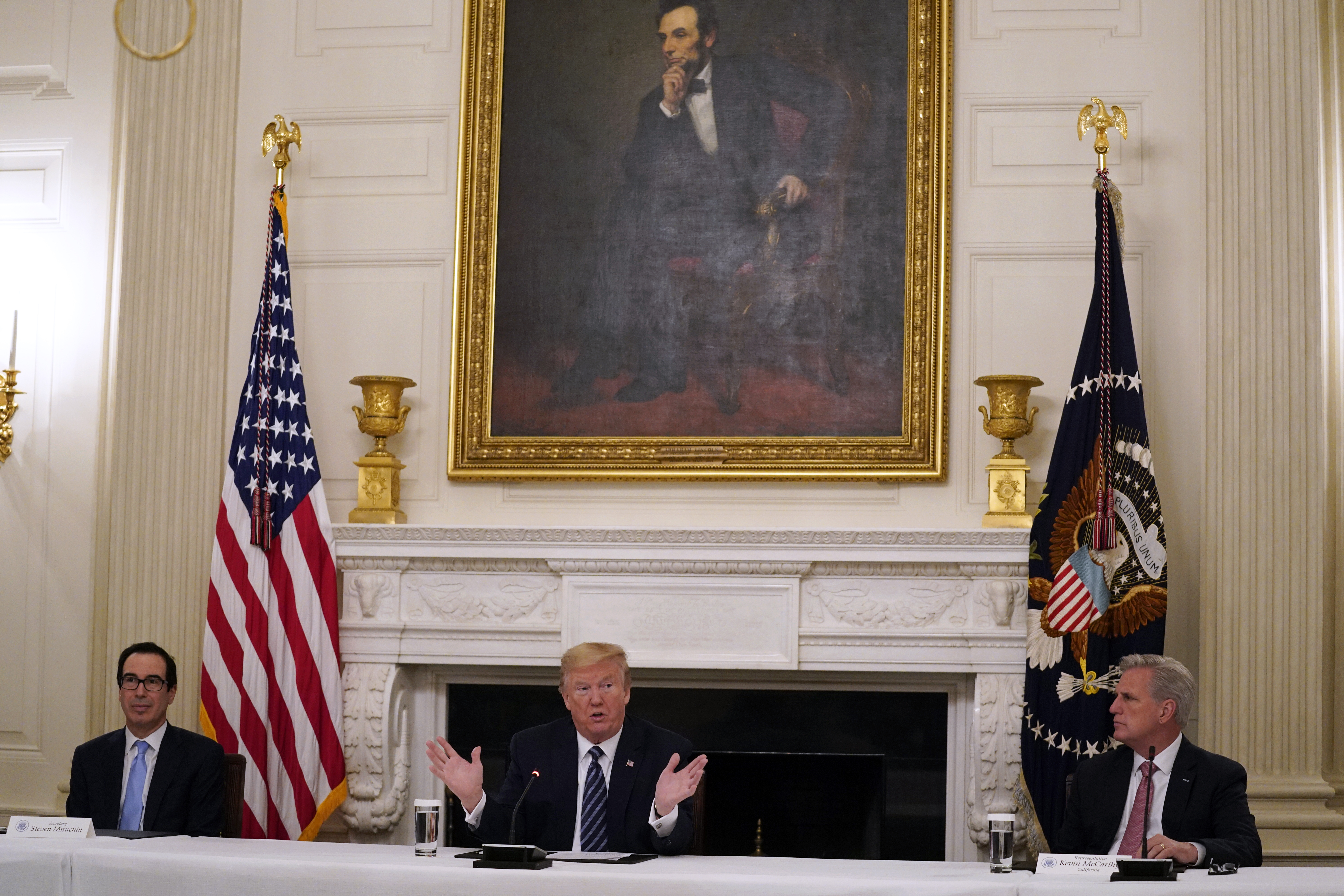 House Minority Leader Kevin McCarthy of Calif., right, and Treasury Secretary Steven Mnuchin, left, listen as President Donald Trump speaks during a meeting with Republican lawmakers, in the State Dining Room of the White House on May 8, 2020, in Washington.
