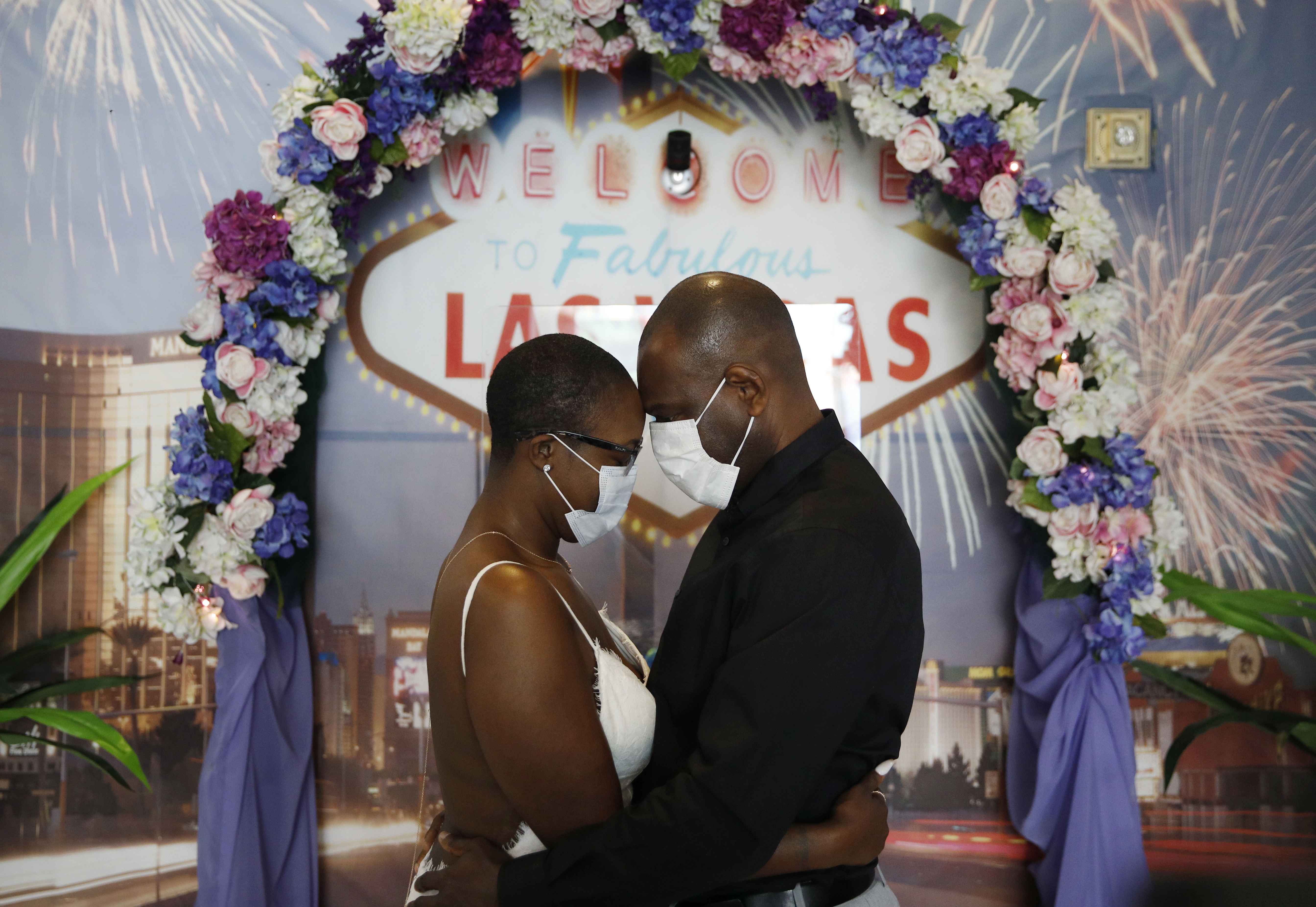 LaTahja Frazier, left, and Laborskie Frazier pose for their wedding photographer after getting married at The Little Neon Chapel, May 10, 2020, in Las Vegas.