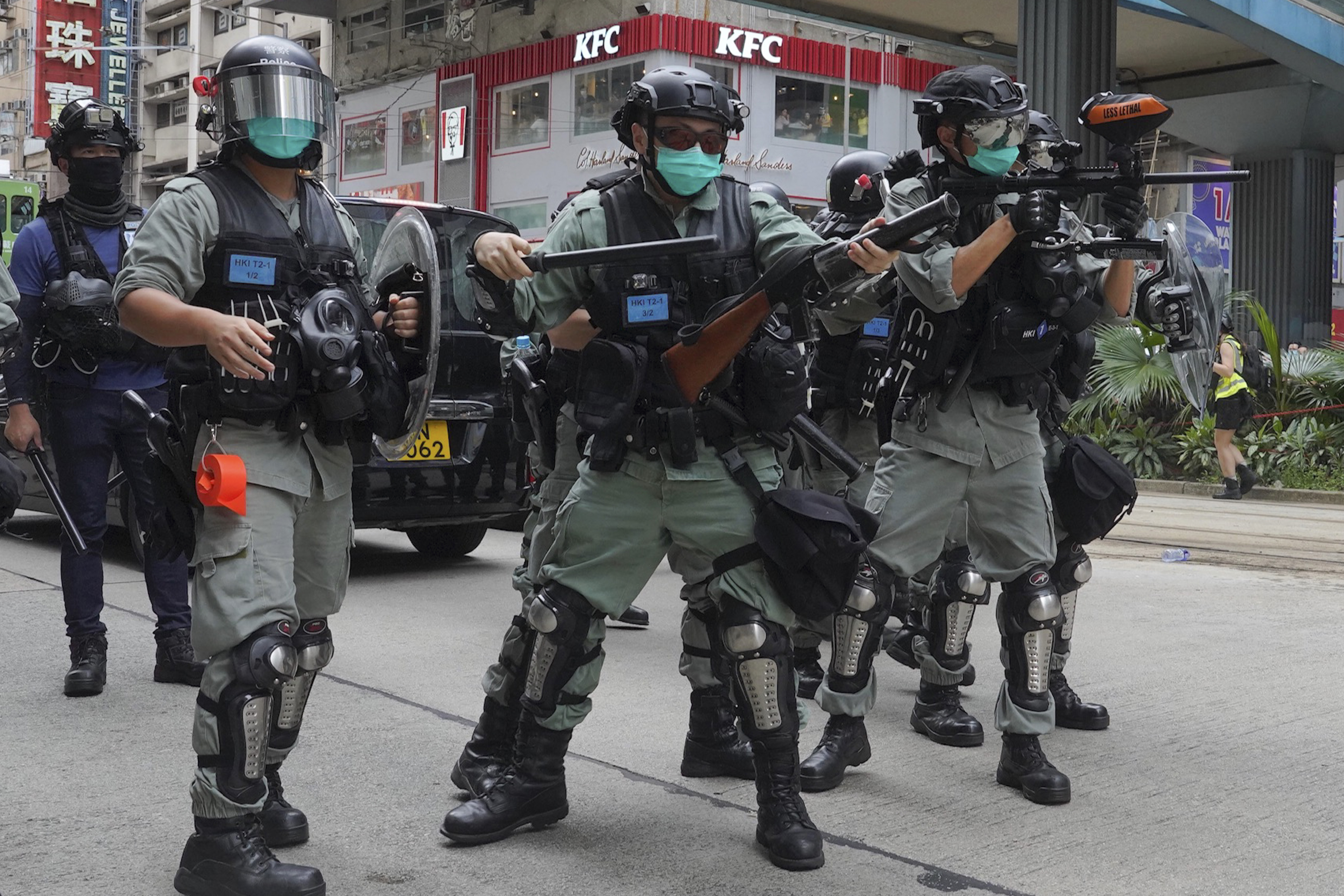 Hong Kong riot police fire tear gas as hundreds of protesters march along a downtown street during a pro-democracy protest against Beijing's national security legislation in Hong Kong, Sunday, May 24, 2020.