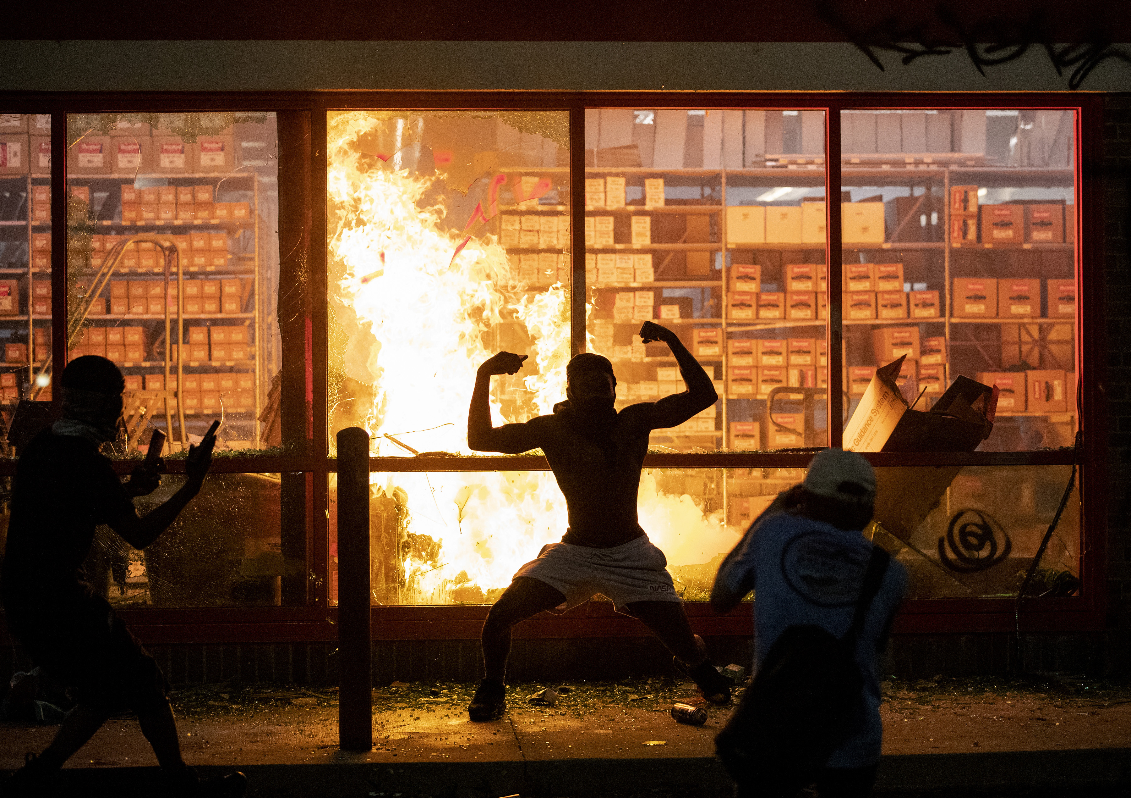 A man poses for photos in front of a fire at an AutoZone store, while protesters hold a rally for George Floyd in Minneapolis on Wednesday, May 27, 2020.