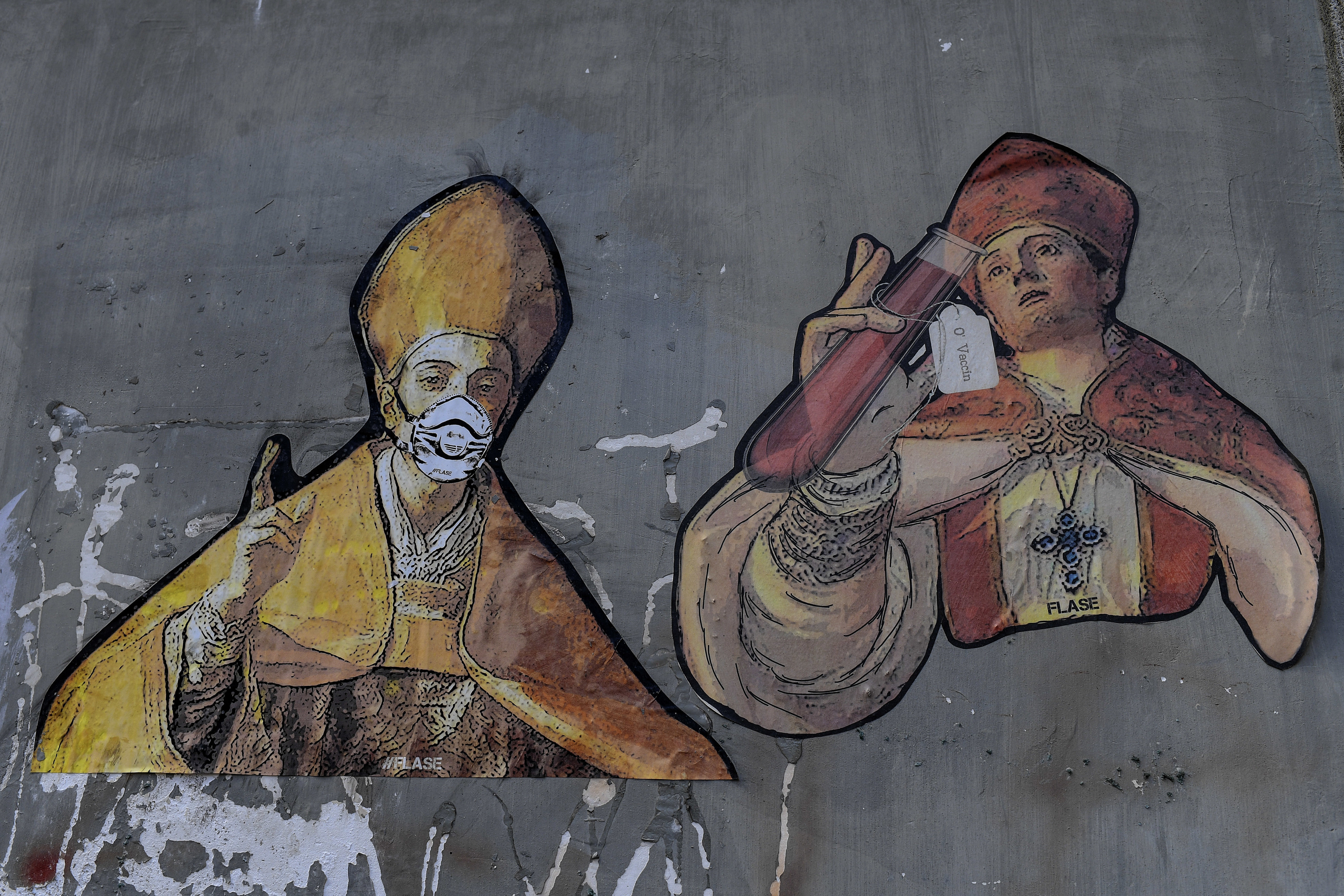 A mural depicting two figures of Saint Gennaro, patron of Naples, with a protective mask and an ampule with the label  The vaccine  written in Napolitan on a wall in the city's downtown, on May 11, 2020.