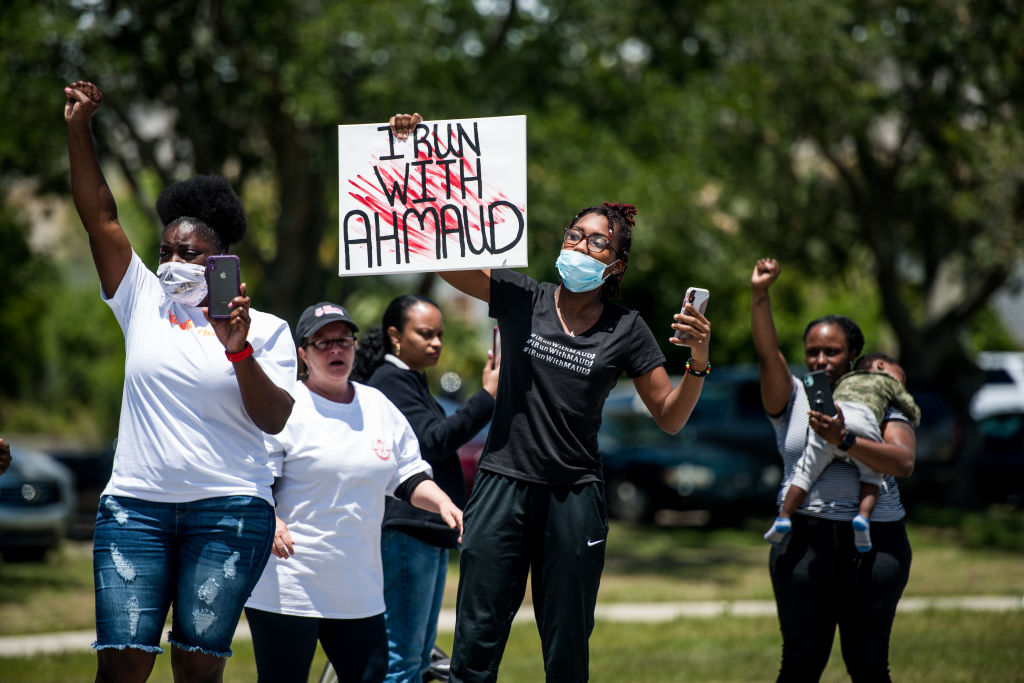 Demonstrators raise their fists at a parade of passing motorcyclists riding in honor of Ahmaud Arbery at Sidney Lanier Park on May 9 in Brunswick, Georgia. Arbery was shot and killed while jogging in the nearby Satilla Shores neighborhood on Feb. 23.