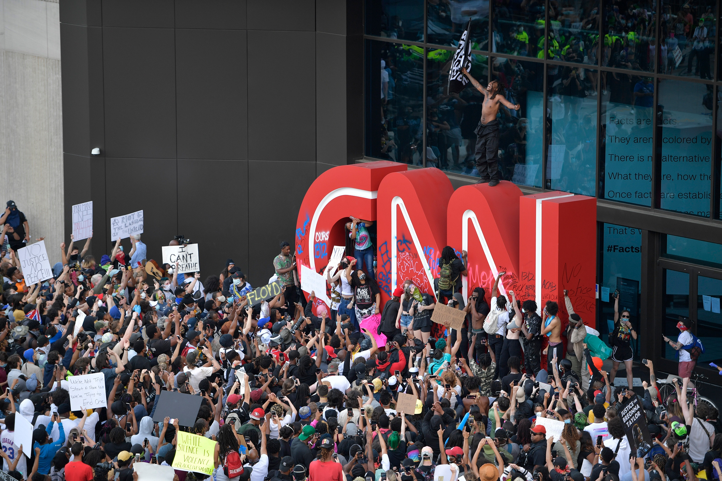 Demonstrators paint on the CNN logo during a protest march in Atlanta, Ga., May 29, 2020. The protest started peacefully earlier in the day before demonstrators clashed with police.