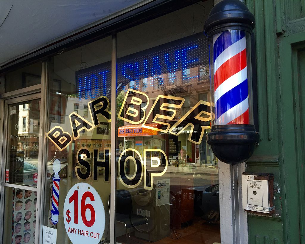 The exterior glass facade of a ground floor commercial storefront Barber Shop with a traditional barbers pole - Park Slope, Brooklyn, NYC September 25, 2015.