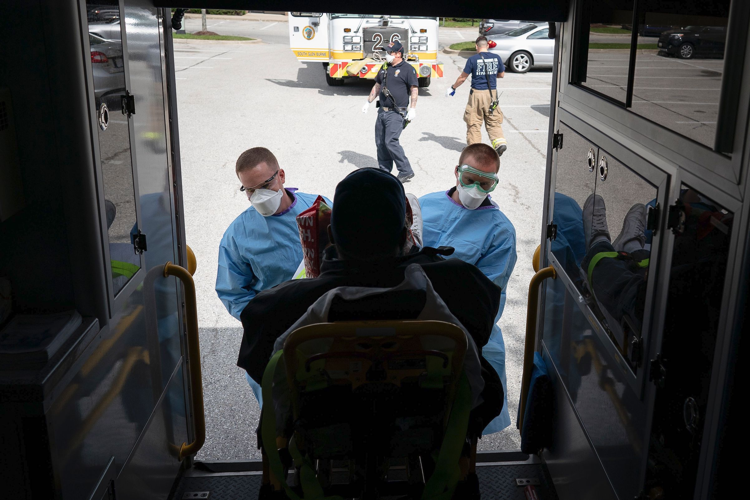 Paramedics with Anne Arundel County Fire Department load a presumptive COVID-19 patient onto the ambulance on April 21, 2020, in Glen Burnie, Md.