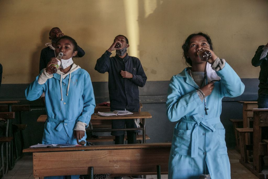 Students at the J.J. Rabearivelo High School in Antananarivo, Madagascar drink from bottles of Covid Organics, a herbal tea, touted by  President Andry Rajoelina as a powerful remedy against the COVID-19 coronavirus,  on April 23 2020