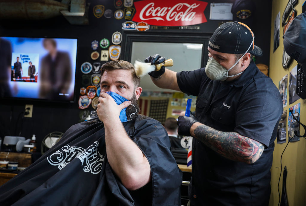 Rusty Razor Barber Shop co-owner John Hopping cuts Norman Bettencourt's hair on the first day of reopening since the coronavirus shutdowns over one month prior in Kittery, ME on May 1, 2020.