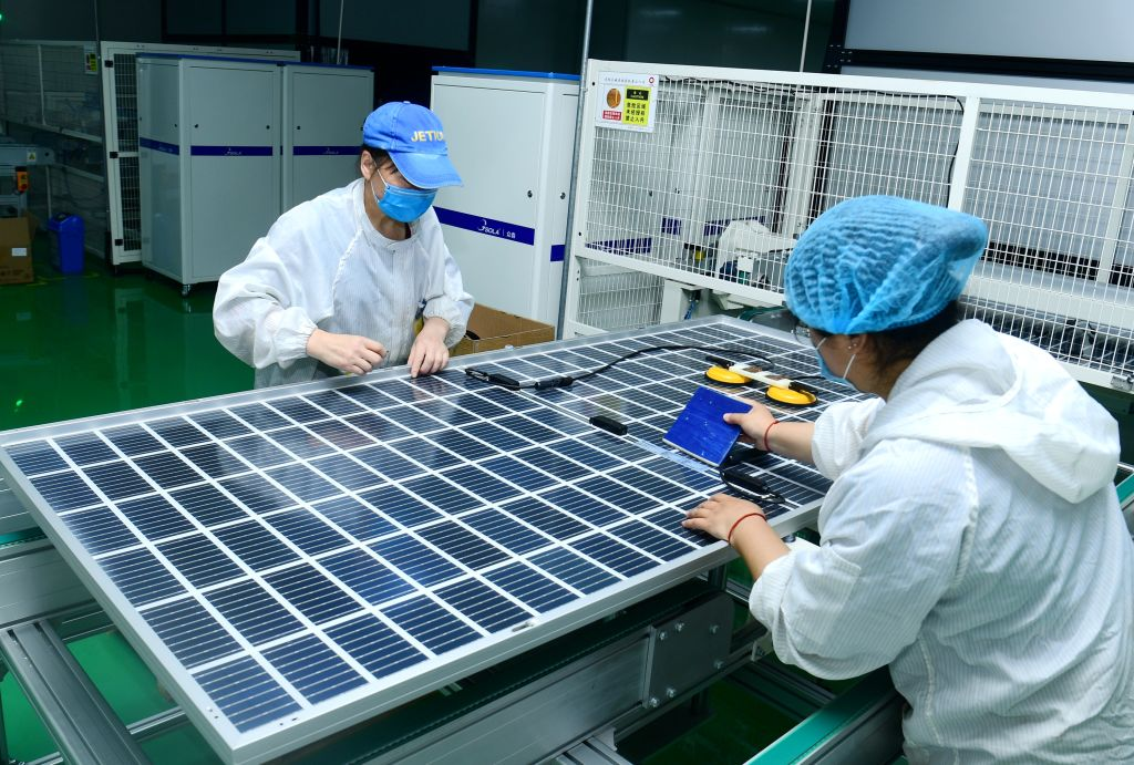 Two workers are on the automatic assembly line to make photovoltaic high-efficiency solar modules in Hai'an City, China, on May 8, 2020.