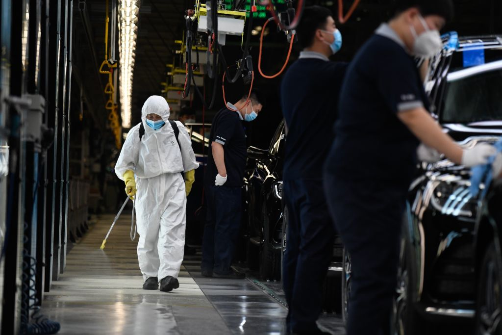 A cleaner wearing protective gear sprays disinfectant along a production line at a Mercedes Benz automotive plant during a media tour organised by the government in Beijing on May 13, 2020, as the country's industrial sector starts again following shutdowns during the COVID-19 coronavirus outbreak.