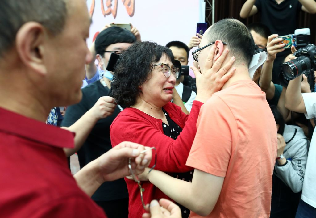 This photo taken on May 18, 2020 shows Mao Yin (R) reuniting with his mother Li Jingzhi (C) and father Mao Zhenping (L) in Xian, in China's northern Shaanxi province.