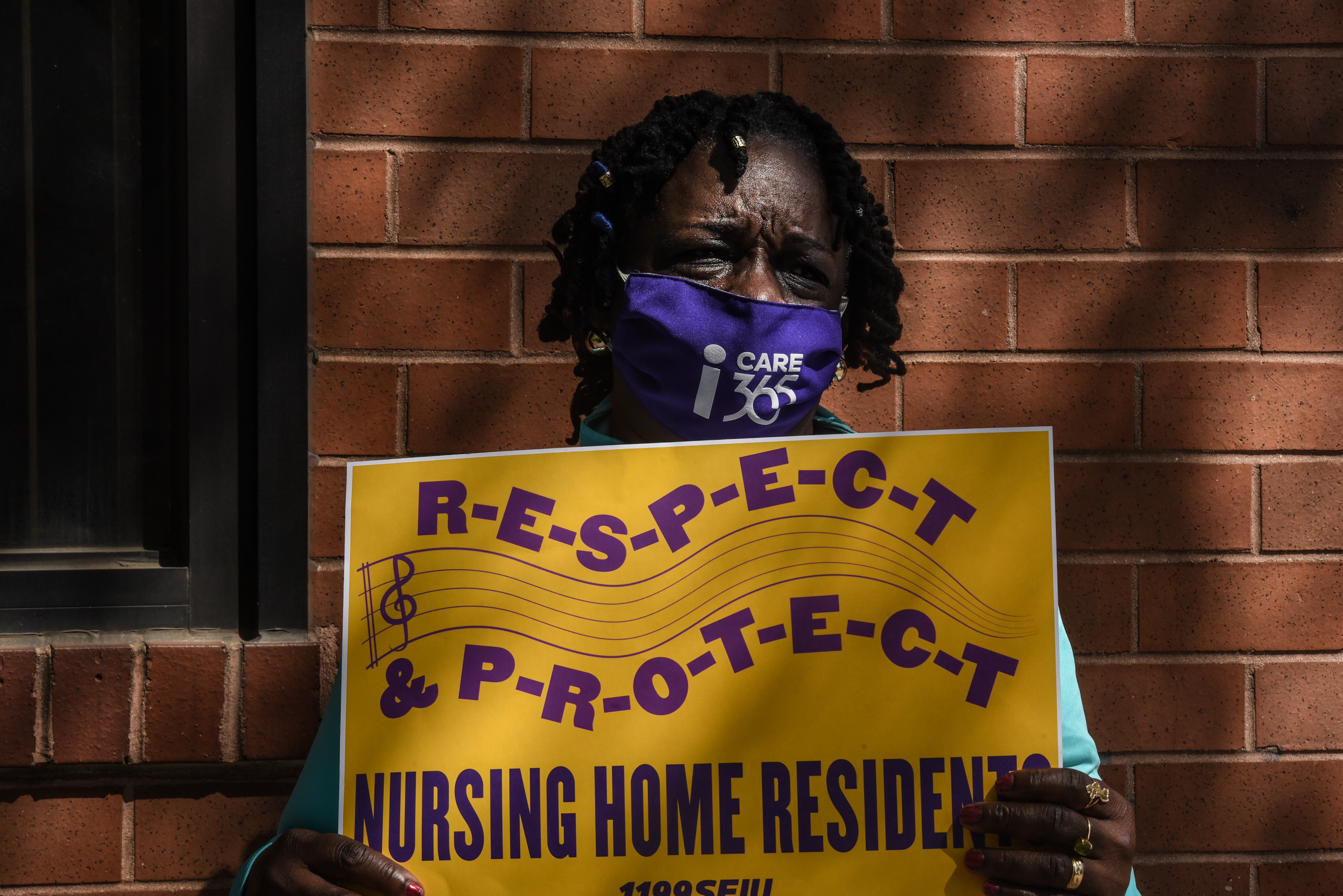 A nursing home worker participates in a vigil outside of a nursing home in Brooklyn, N.Y. on May 21, 2020. Workers say they need safer conditions to better protect nursing home residents and the people who care for them from the coronavirus.