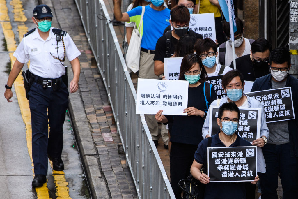 Pro-democracy protesters hold black placards that translate as  National Security Law comes to Hong Kong, Hong Kong becomes Xinjiang, Stanley Prison becomes Qincheng Prison, Hong Kongers Revolt , as they march towards the Chinese Liaison Office in Hong Kong on May 22, 2020.