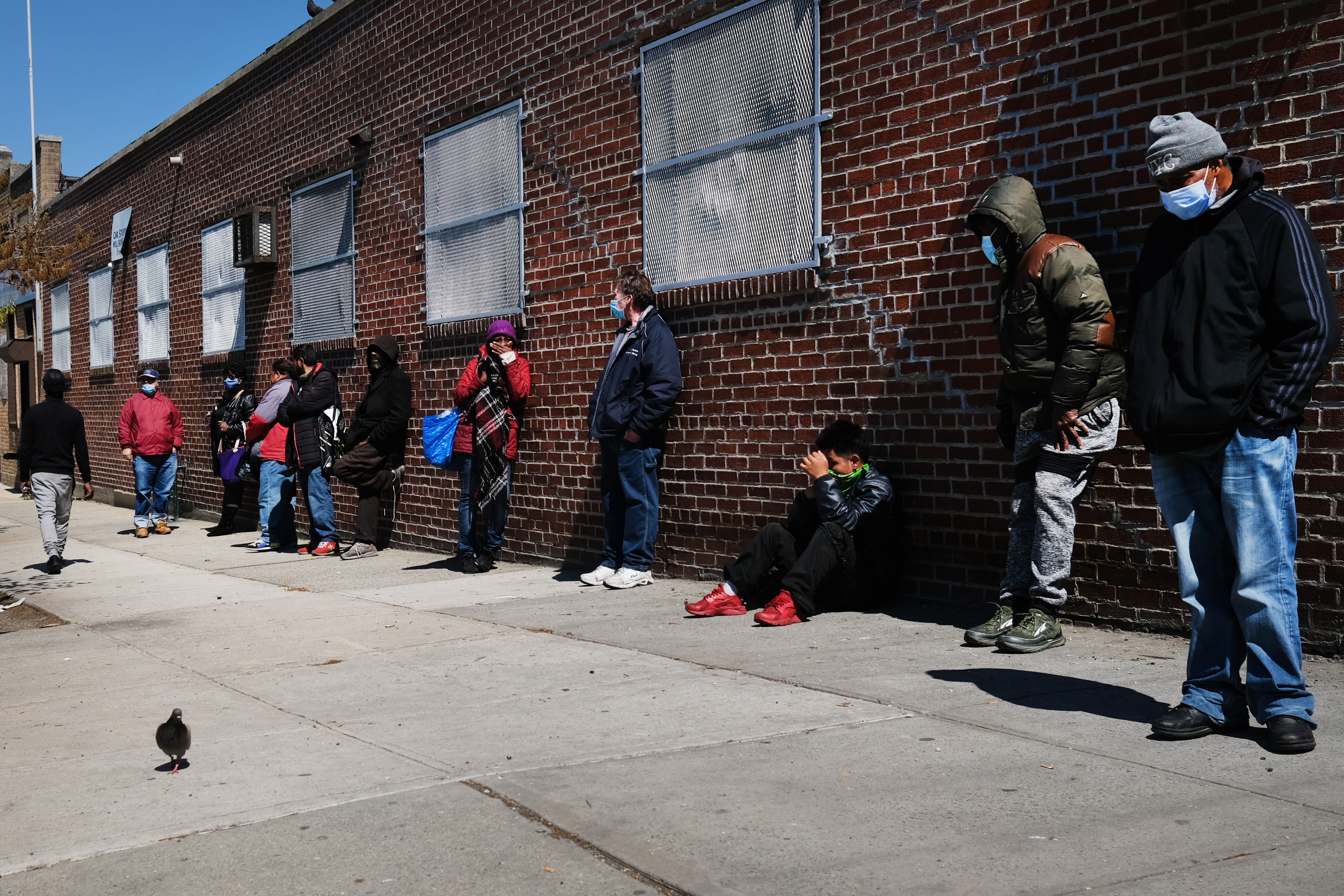 People wait in line to receive food at a food bank on April 28, 2020 in Brooklyn, New York.