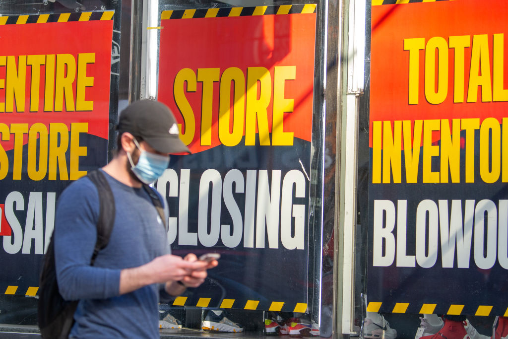 A man wearing a mask walks past 'Store closing' signs amid the coronavirus pandemic in New York City on May 7, 2020.