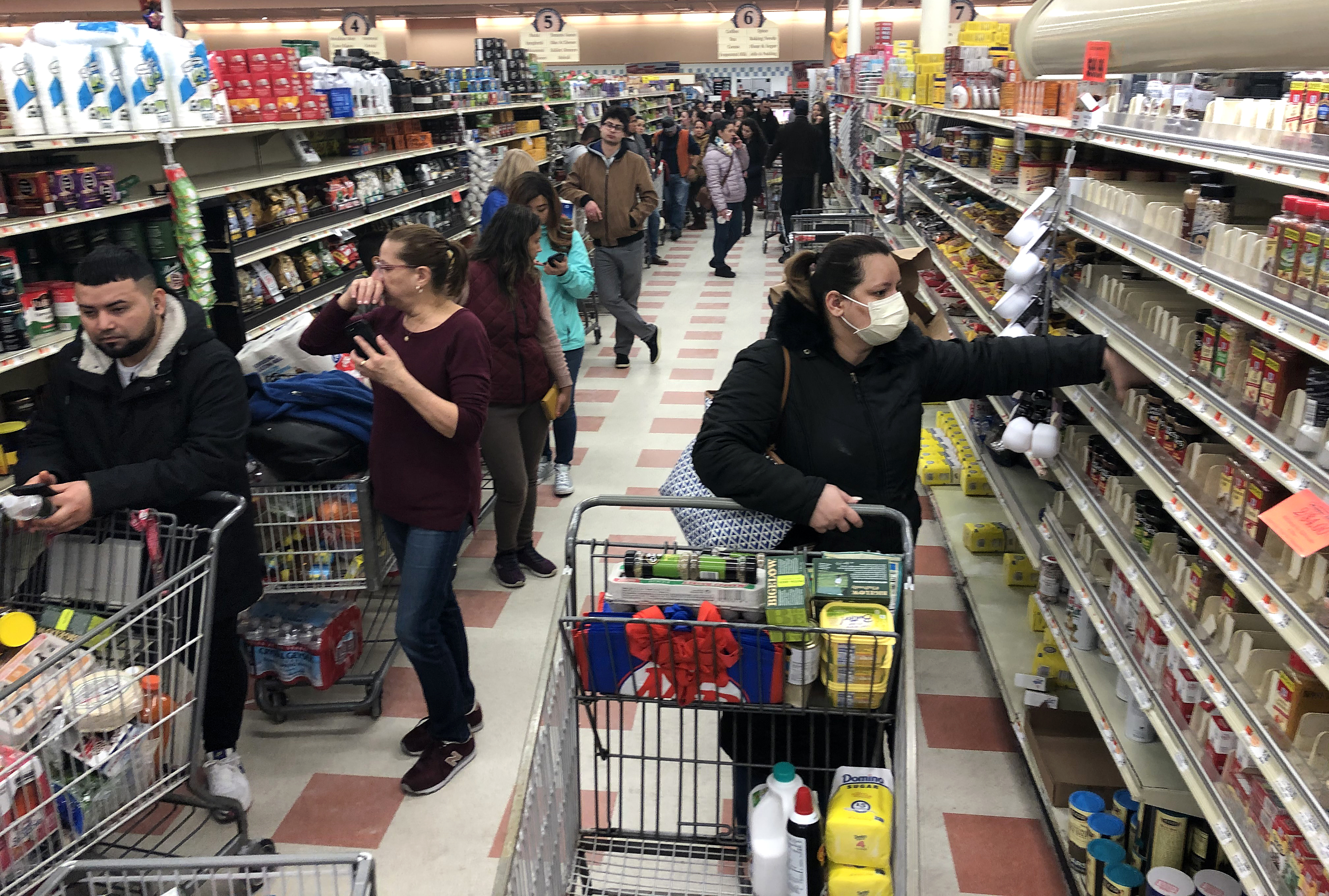 A woman in a protective mask shops as a line of shoppers stretch to the back of the store waiting to check-out at the Market Basket in Chelsea, Mass. on March 13, 2020.