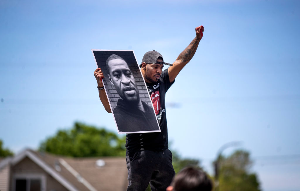 A protester holds a photo of George Floyd in front of the Cup Food Store where he was killed in Minneapolis, Minnesota on May 28, 2020.