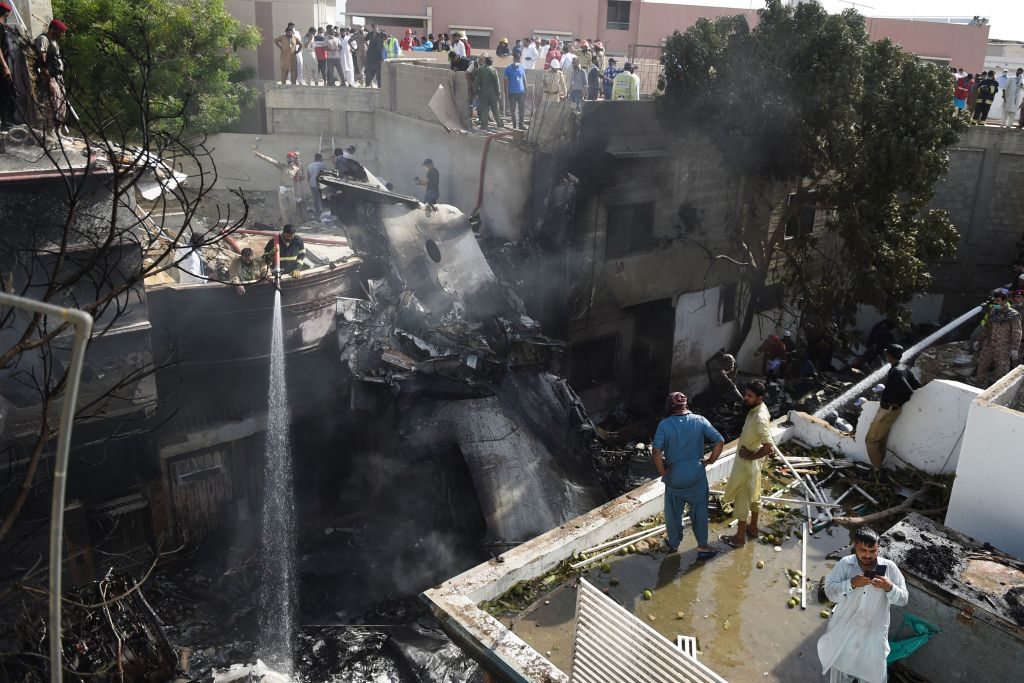 Firefighters spray water on the wreckage of a Pakistan International Airlines aircraft after it crashed at a residential area in Karachi on May 22, 2020.