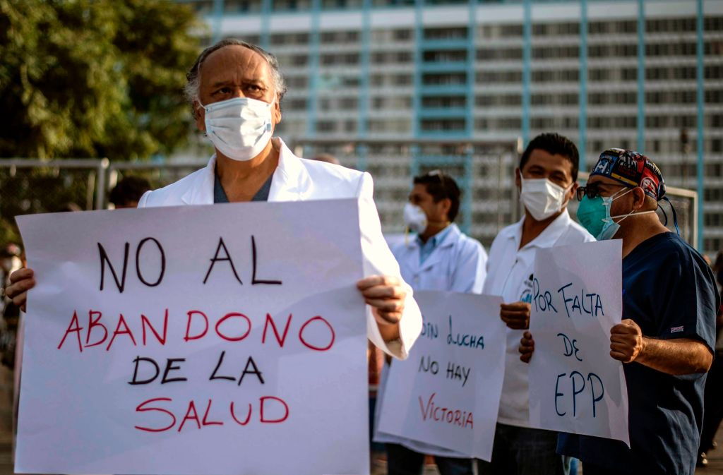Health workers protest for the lack of security equipment demanding the resignation of Peruvian Health Minister Victor Zamora with a sign reading No to the abandonment of healthcare outside the Edgardo Rebagliati public hospital in Lima on May 13, 2020.
