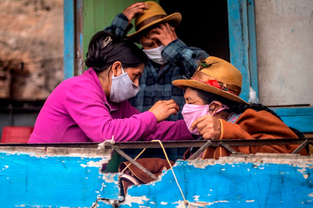 A woman arranges a her mother's face mask at their house of the Pamplona Alta section on the southern outskirts of Lima on May 28, 2020.