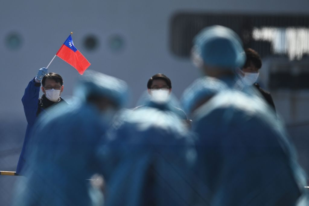 A man holds a Taiwan flag as passengers disembark from the Diamond Princess cruise ship due to fears of COVID-19 in Yokohama, Japan on Feb. 21, 2020.