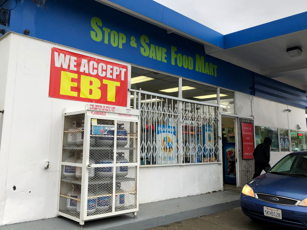 A sign noting the acceptance of electronic benefit transfer (EBT) cards that are used by state welfare departments to issue benefits is displayed at a convenience store on Dec. 4, 2019 in Richmond, Calif.