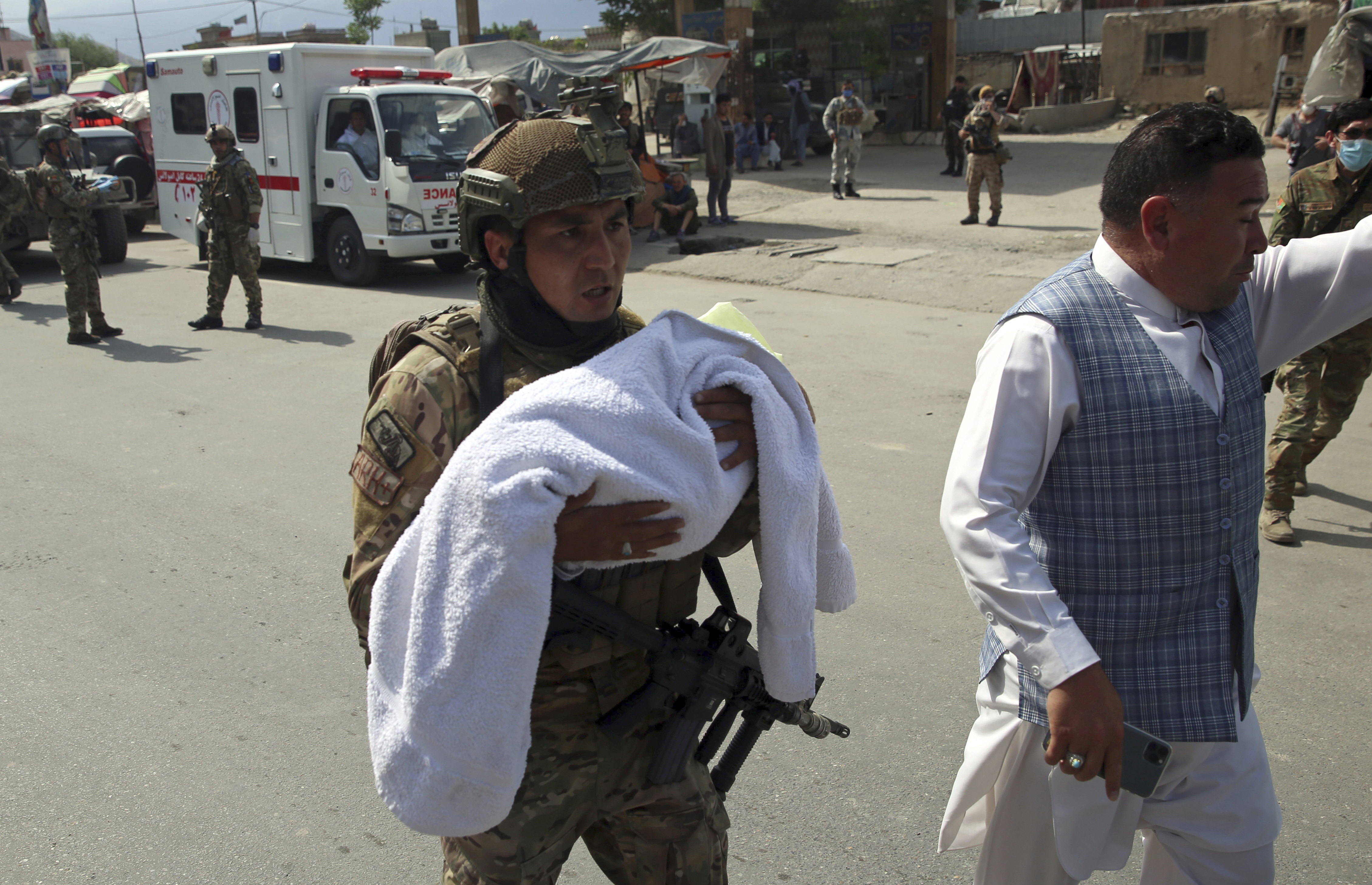 An Afghan security officer carries a baby after gunmen attacked a maternity hospital, in Kabul, Afghanistan, on  May 12, 2020.