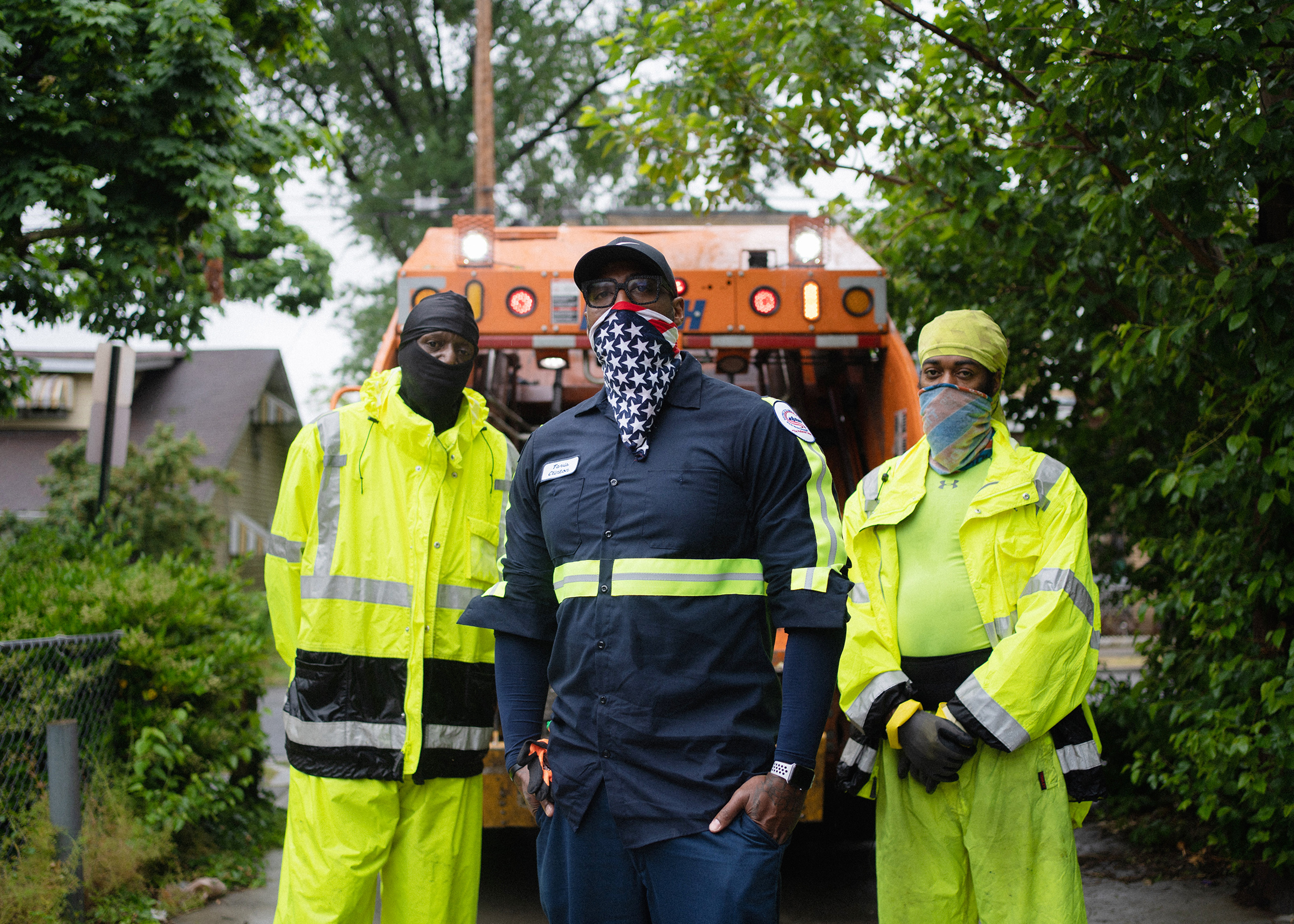 Sanitation crew chief Tavis Clinton, center, and sanitation workers Arvel Baylor, left, and Maurice Eley, right, stand behind their waste collection vehicle in Washington, D.C., on May 22, 2020.