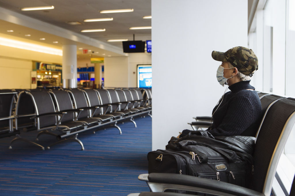 A traveler wearing a protective mask sits at a gate in Terminal 5 at John F. Kennedy International Airport (JFK) in New York, U.S., on Thursday, April 9, 2020.