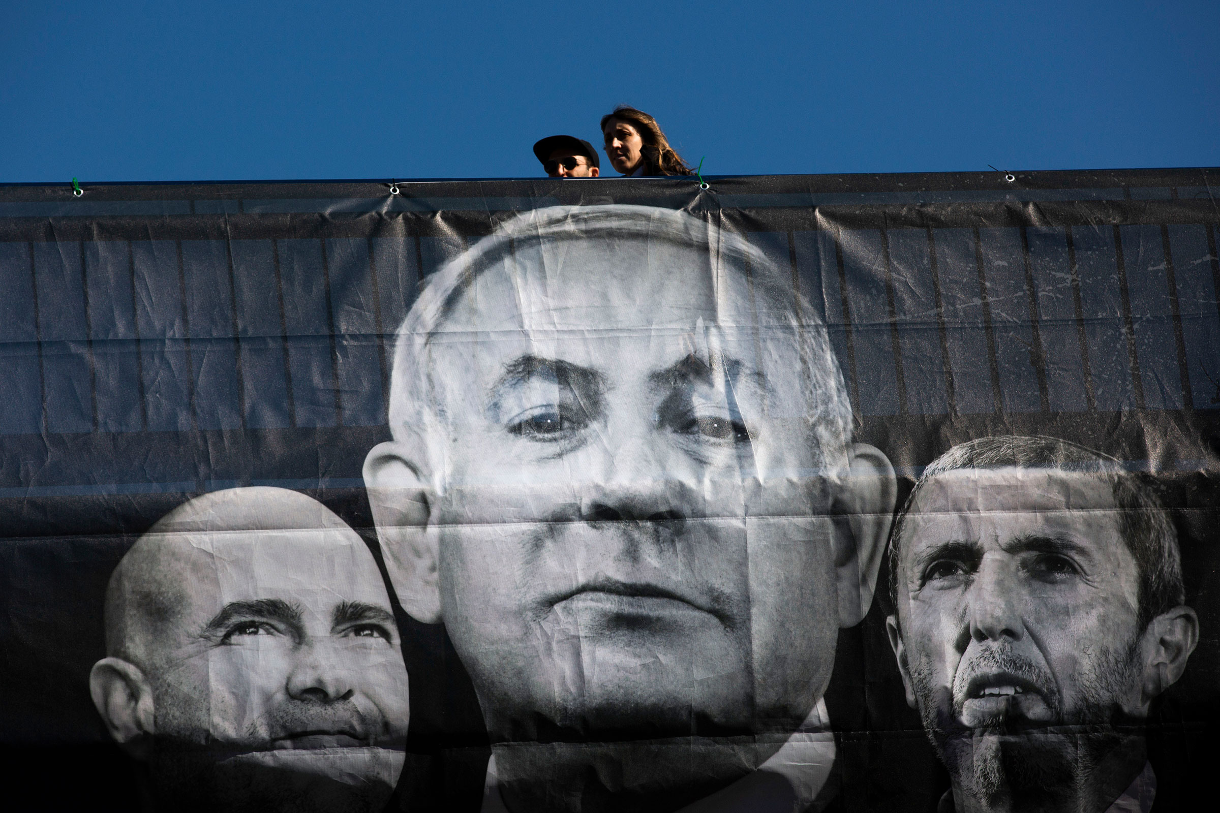 People walk next to an election campaign billboard for Blue and White party showing Israeli Prime Minister Benjamin Netanyahu, and his party members, Amir Ohana, left and Rafi Peretz, right, in Tel Aviv on March 1, 2020.
