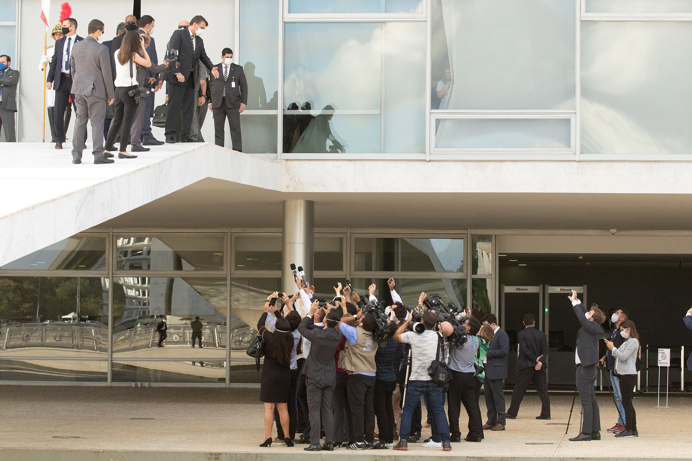 Brazil's far-right President Bolsonaro addresses journalists from outside the Planalto Palace, the official presidential workplace, in Brasília on May 12 as cases of COVID-19 surge across the country