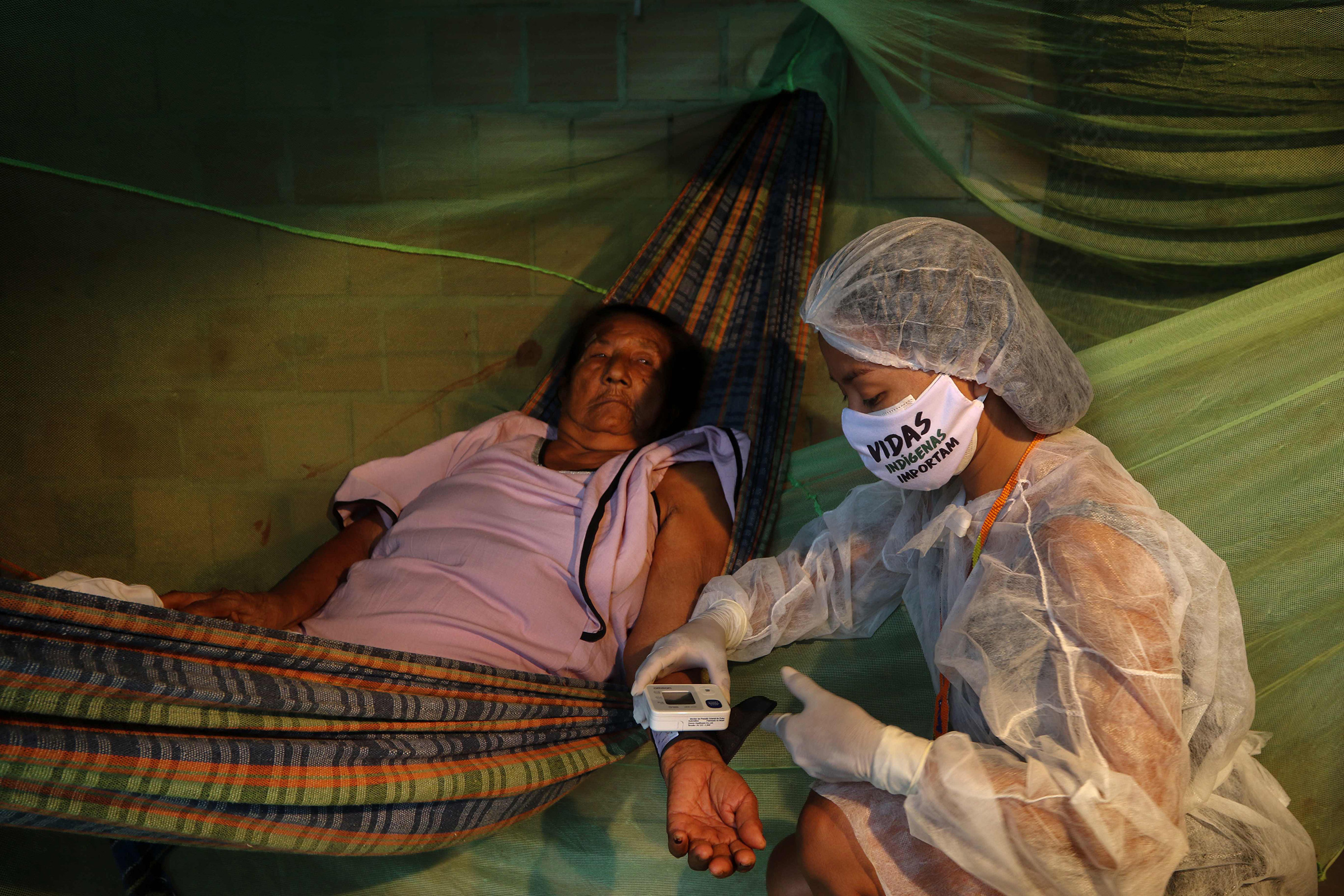 Nurse technician Vanda Ortega Witoto, 32, takes care of a patient in Parque das Tribos, an indigenous community near Manaus, the capital of Brazil's northern Amazonas state