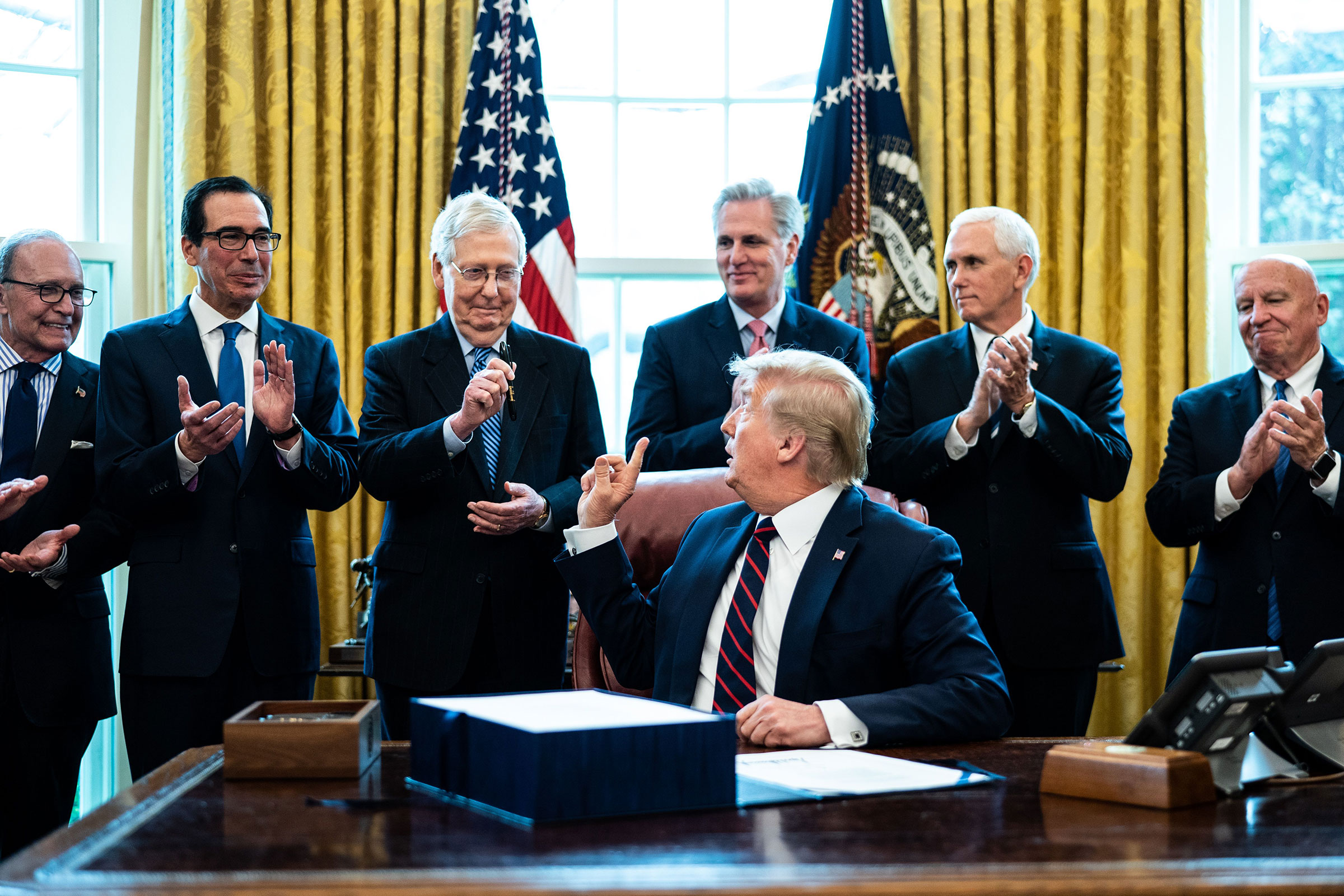 President Donald Trump hands a pen to Republican Senate Majority Leader Mitch McConnell during a signing ceremony for the The CARES Act in the Oval Office on 27 March 2020.