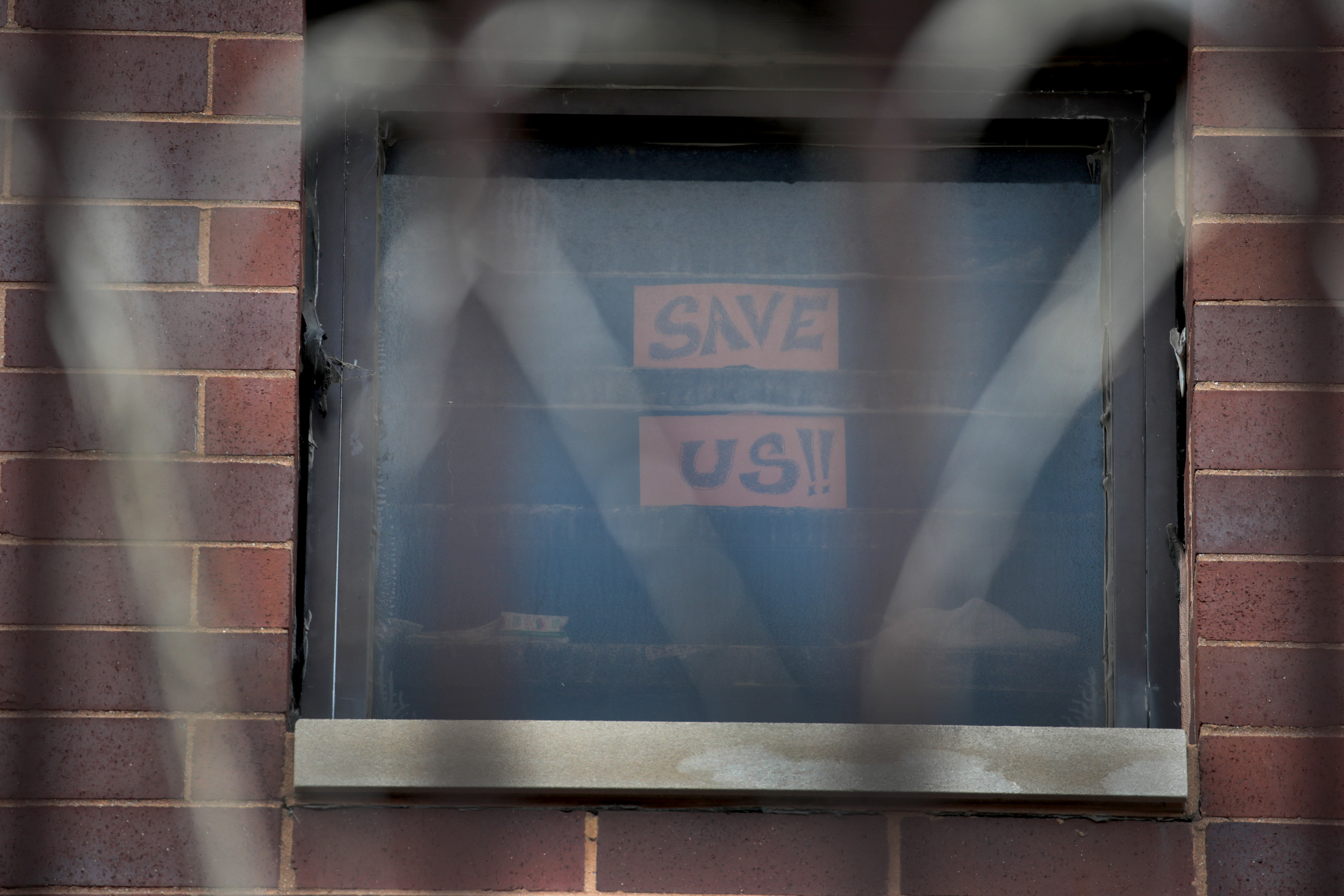 A sign pleading for help hangs in a window at the Cook County jail complex in Chicago, Illinois on April 9, 2020.