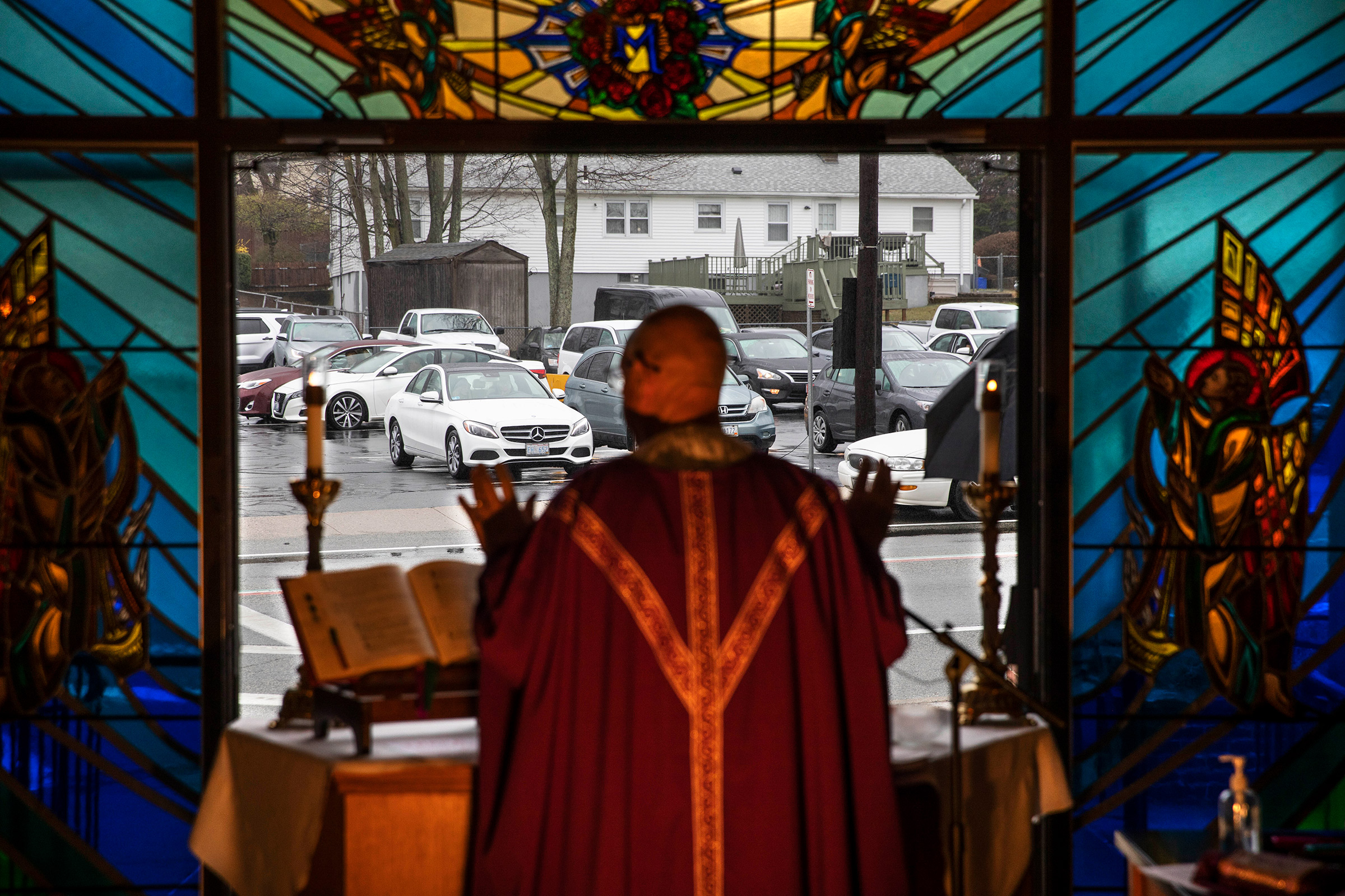 Rev. Peter Gower celebrates Mass from the front door of Our Lady of Grace Catholic Church as worshippers listen over the radio from their cars in the parking lot, Sunday, March 29, in Johnston, R.I.