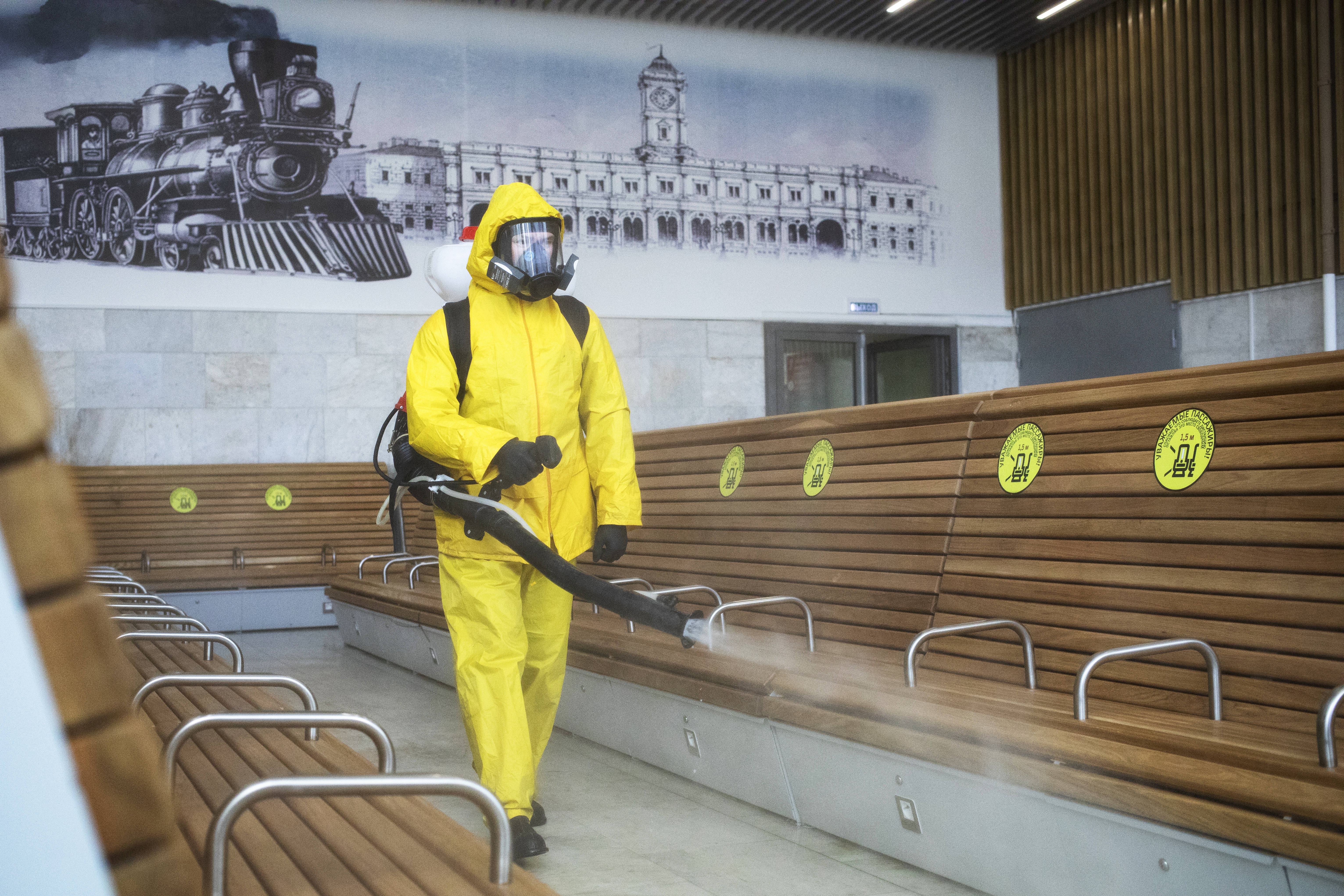 An employee of the Federal State Center for Special Risk Rescue Operations of Russia Emergency Situations disinfects a hall of Leningradsky railway station in Moscow, Russia, on May 19, 2020.