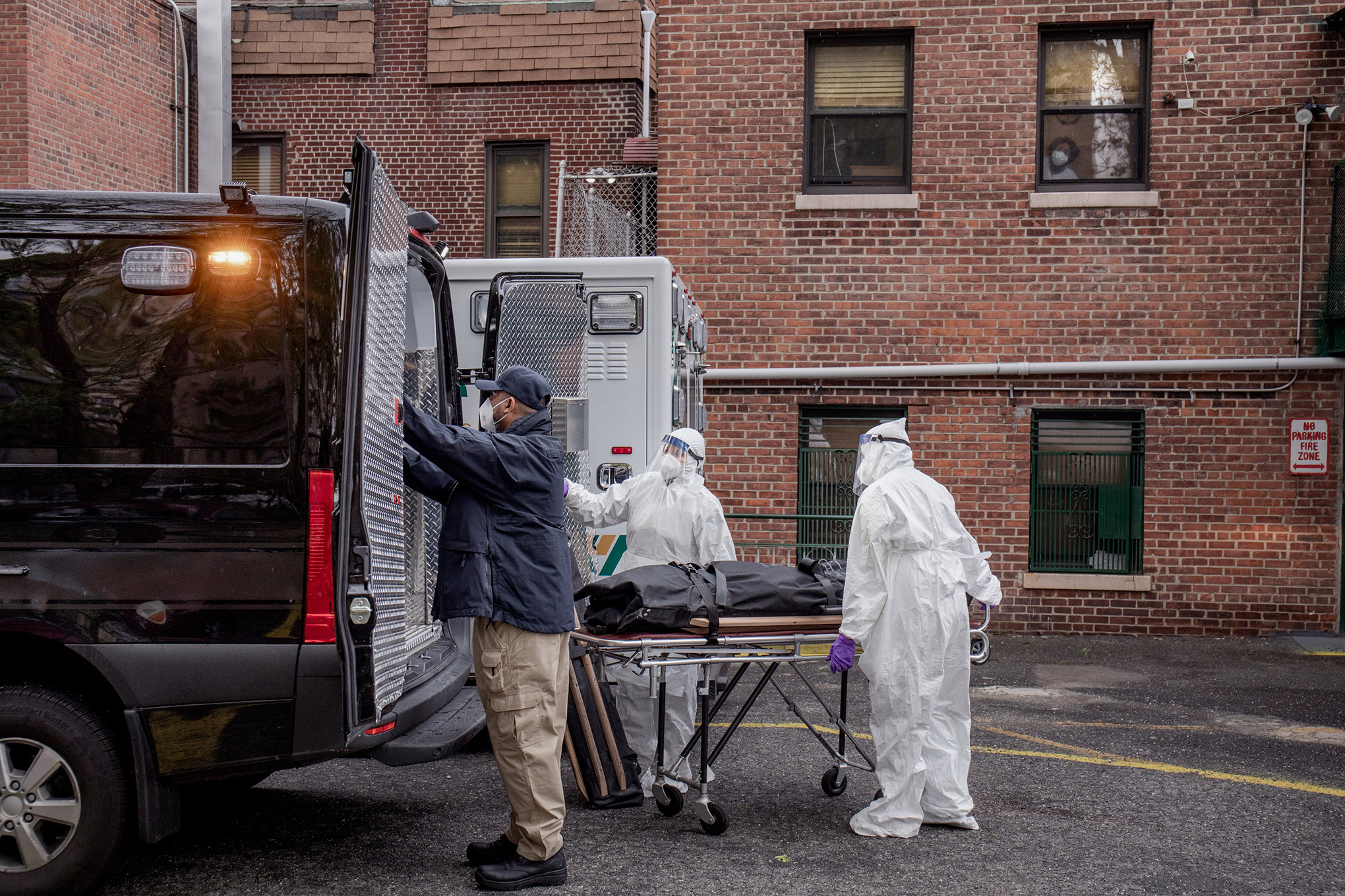 A collection team removes remains from a residence in the Bronx on May 8. Twelve hour shifts have become routine.