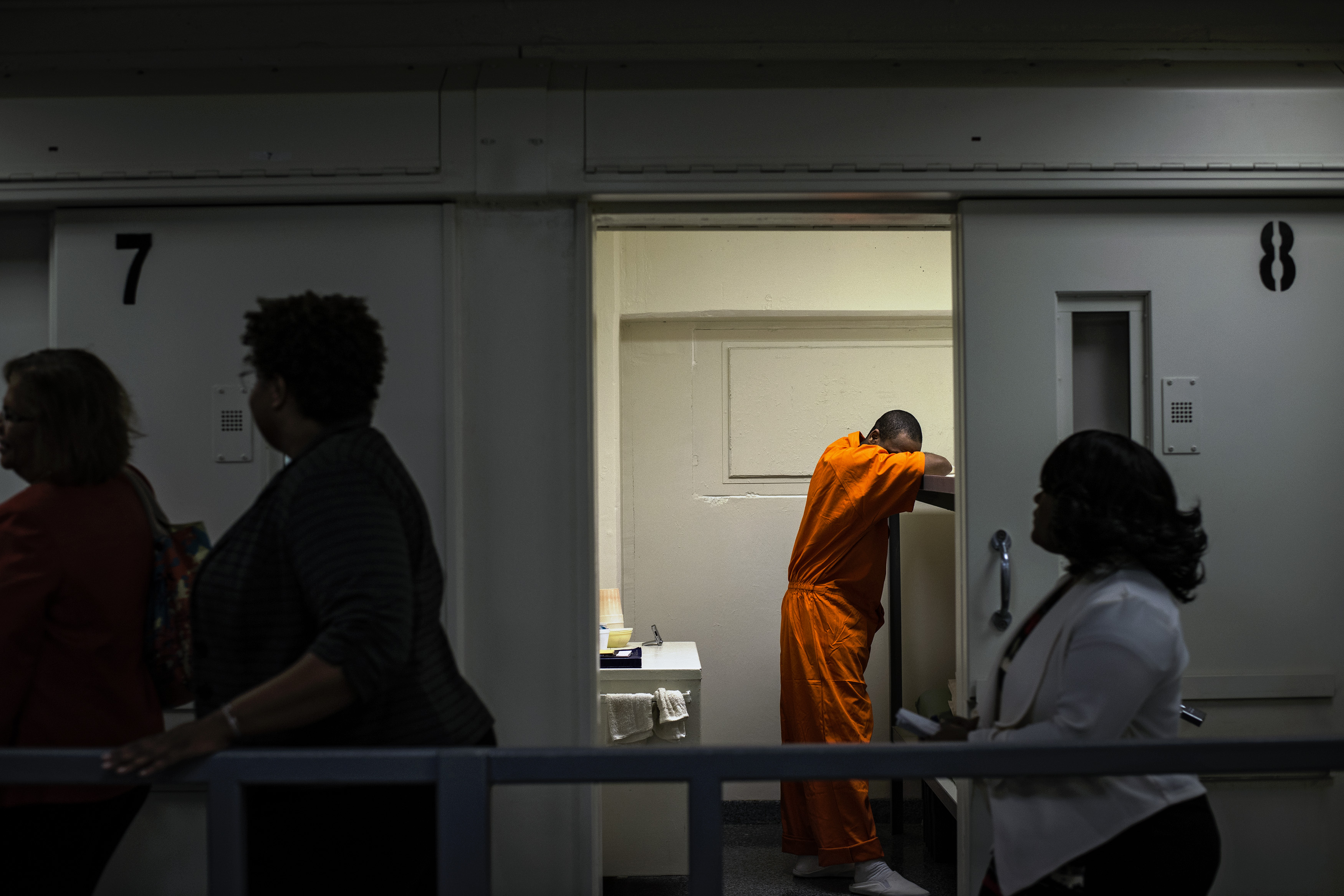 Members of D.C. Mayor Muriel Bowser's entourage walk past an inmate's cell as she tours D.C. Central Jail on September 14, 2015.