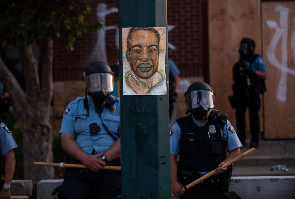 A portrait of George Floyd hangs on a street light pole as police officers stand guard at the Third Police Precinct during a face off with a group of protesters in Minn., Minnesota, May 27, 2020.
